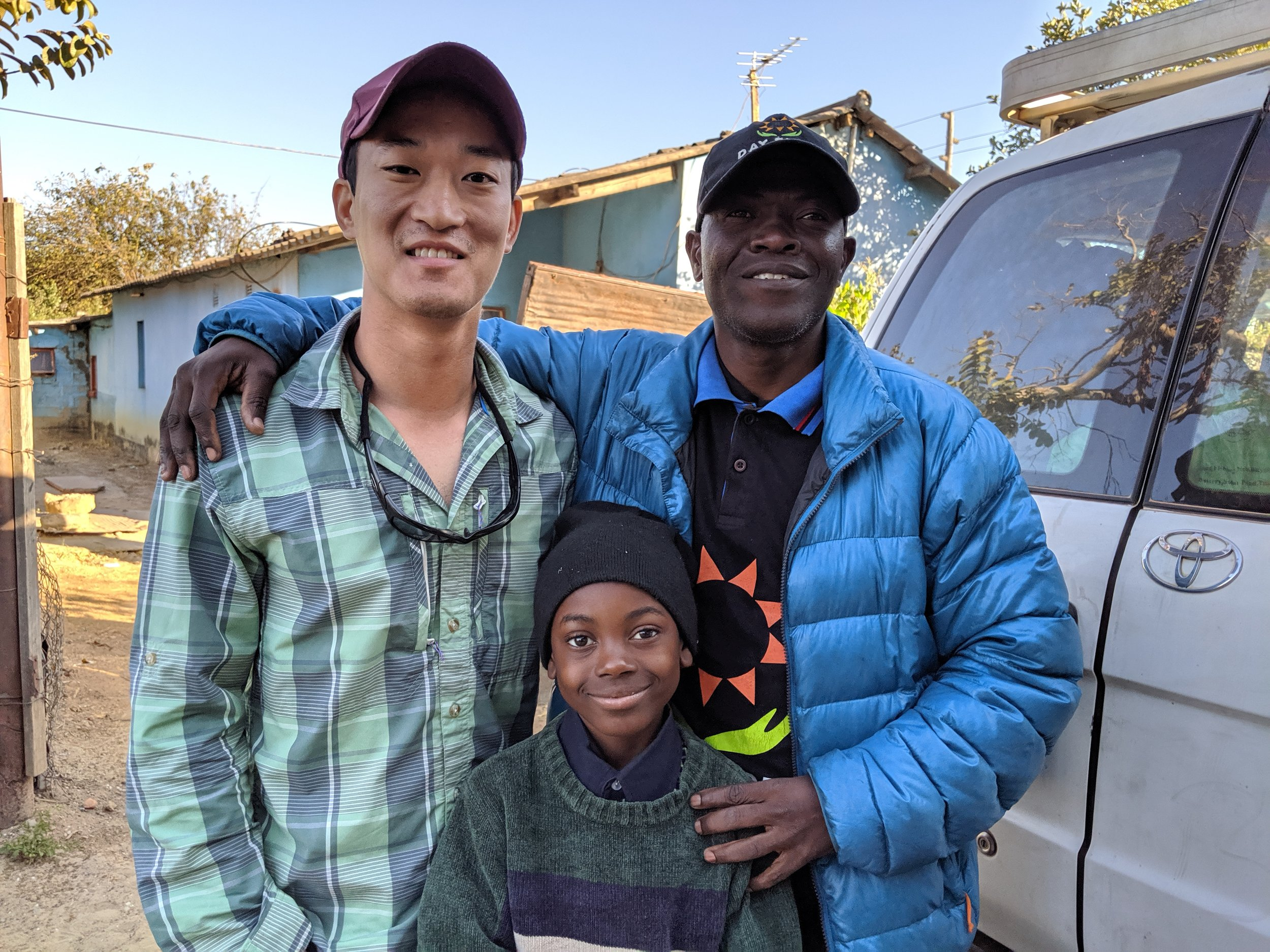 Me, Fred, and Fred's son outside of their home