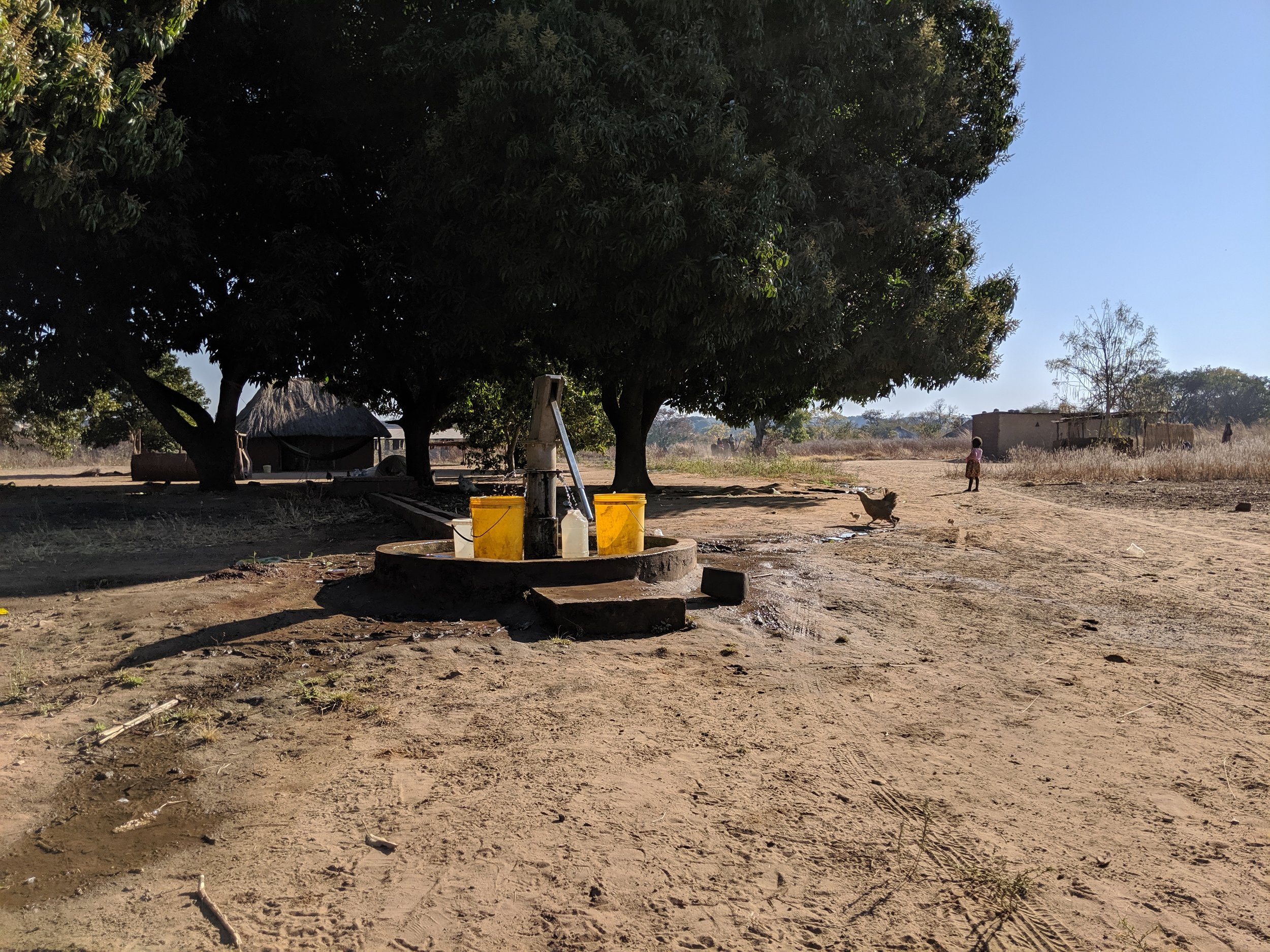 The well/bore hole with hand pump in the center of the village. As the only bore hole within a 1 km radius, many neighboring villages come to use this as well.