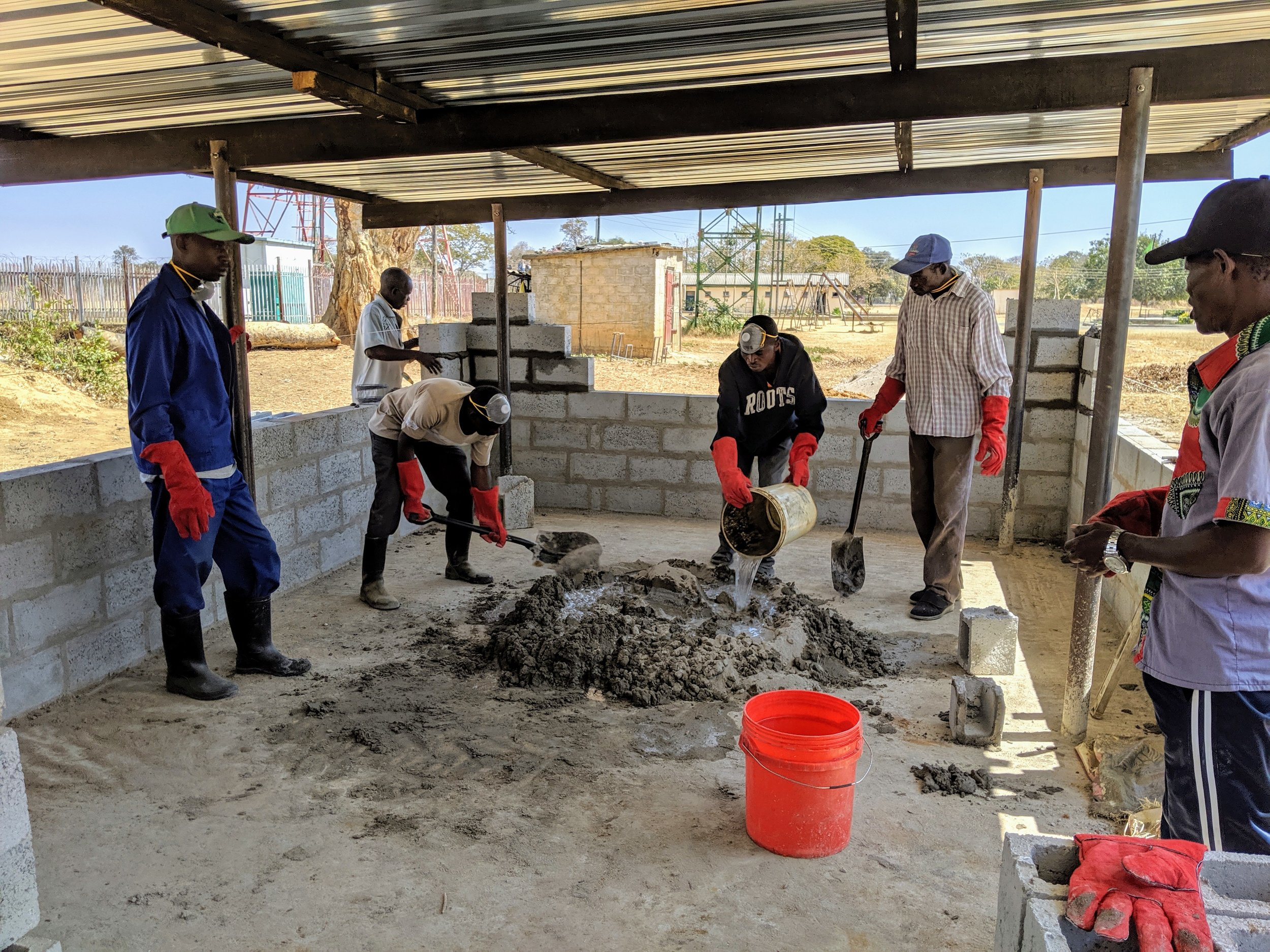 Mixing concrete to finish the wall in the background