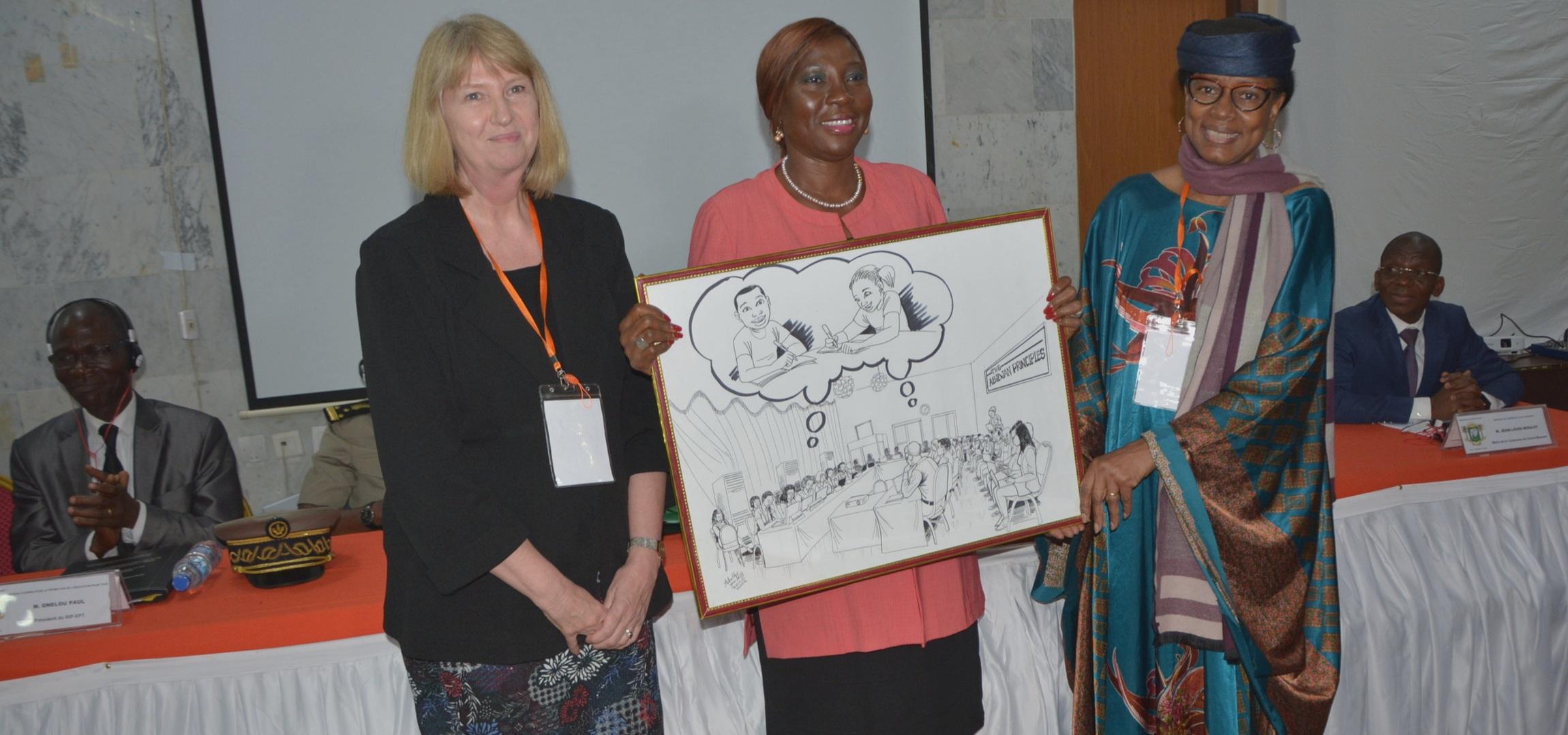 Profesora Ann Skelton, presidenta del Comité de Redacción y Cátedra UNESCO de Derecho de la Educación en África, con Madame Kombou Boly Barry, Relatora Especial de la ONU sobre el derecho a la educación, presenta un dibujo del artista Yannick Ackatchy a la Ministra de Educación de Costa de Marfil, para celebrar la adopción de los Principios de Abidjan.
