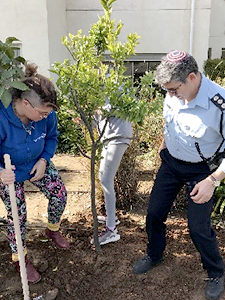 Anna and police officer plant a tree at Beit Ruth