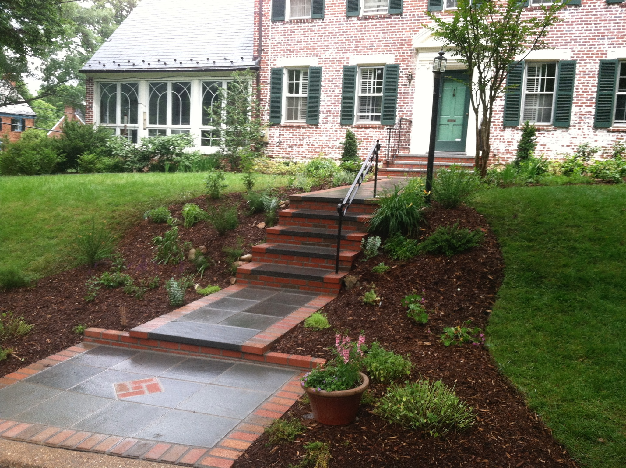 After. New flagstones with brick edges and new plantings.