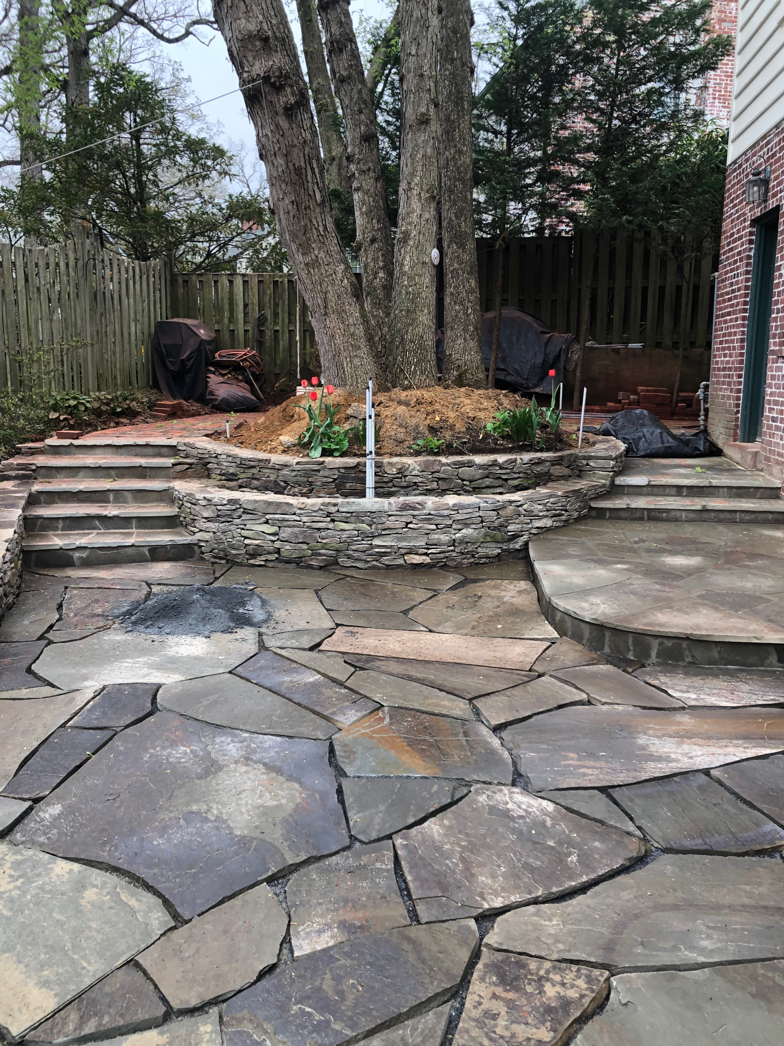 After. Irregular flagstones with tiered garden wall and new steps.