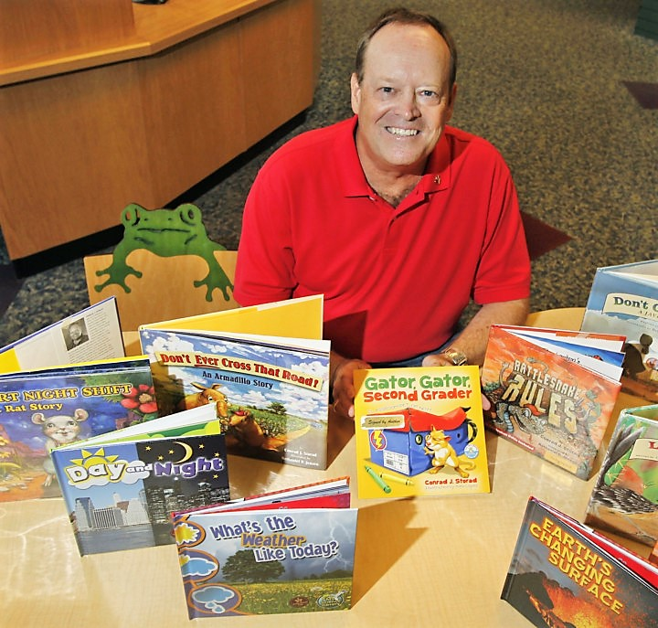 Children's book author Conrad Storad sits in the children's section of the Barberton Public Library surrounded by just a few of the fifty books he has written. Storad will be one of five people from Barberton inducted into the Barberton Walk of Fame.  (Karen Schiely/Akron Beacon Journal)