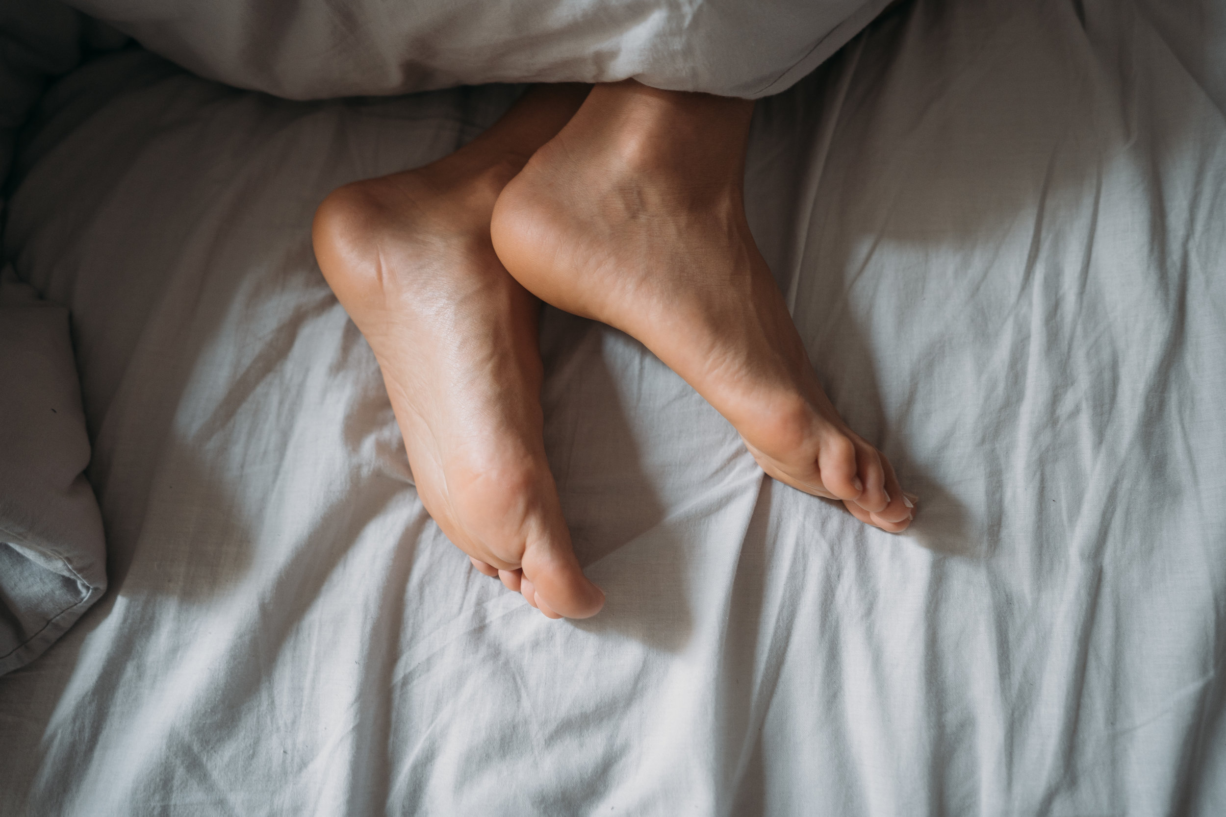 close-up-woman-feet-alone-in-white-bed-W24N7CE.jpg