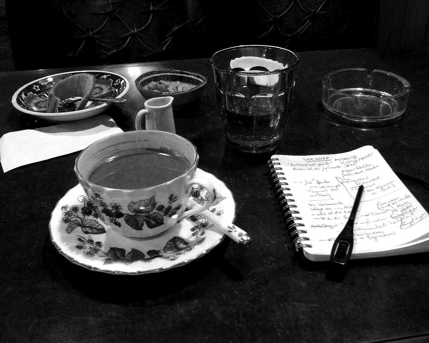 """A Japanese Café, a paradise for smokers who I am not, me scribbling notes about the short story """"Werfen"""" (published in """" Island Universe """") and hailing the queen of the café- a cat"""