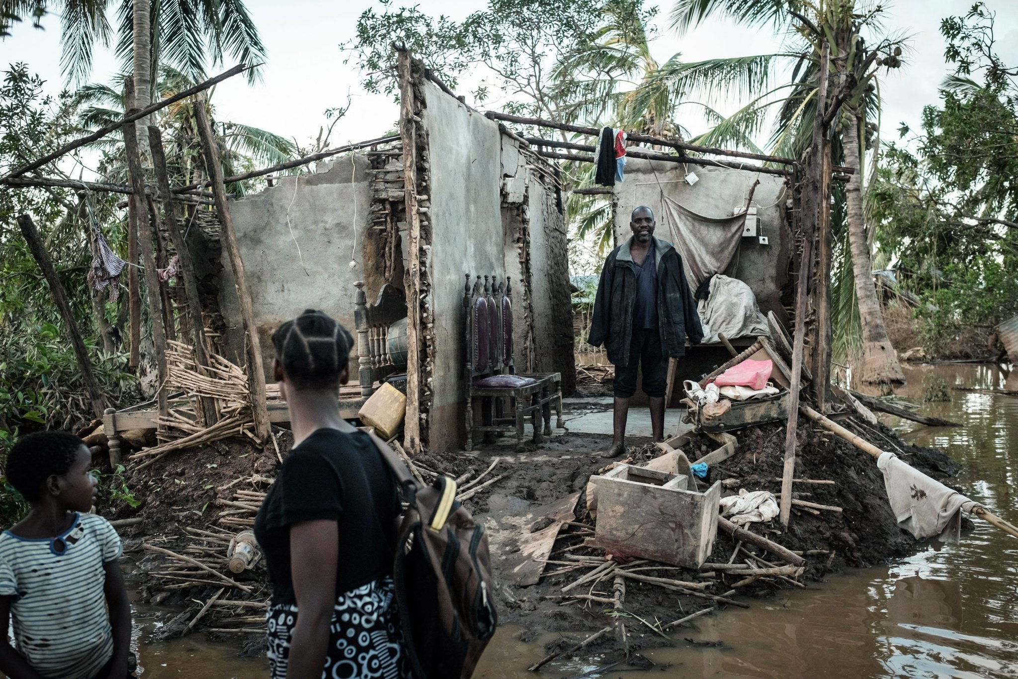 From the remnants of his home, Francisco Simon looked out at his daughters as they went off to sleep in a shelter in Buzi, Mozambique on Friday. Credit Yasuyoshi Chiba/Agence France-Presse — Getty Images