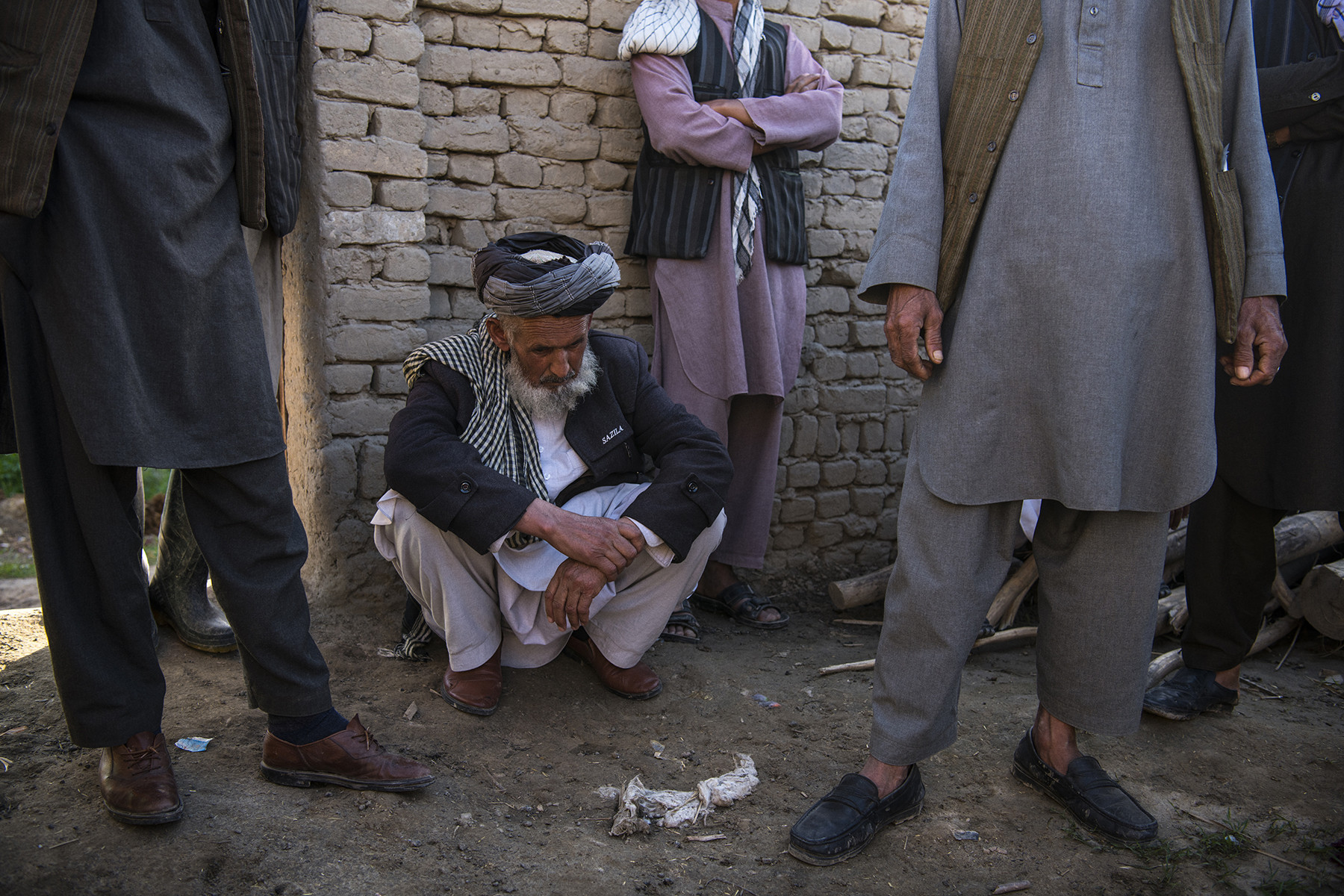 Juma Khan gathers with neighbors on March 31 at the site of what appears to be a U.S. airstrike in which 13 members of an extended family, including his daughter, son-in-law, and numerous grandchildren, were killed in the village of Aqulabul, near Telawka, north of Kunduz, Afghanistan, on March 22. ANDREW QUILTY FOR FOREIGN POLICY