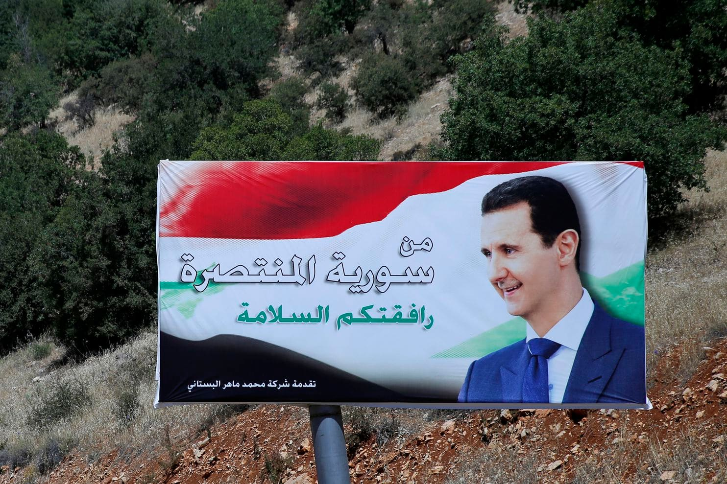 """A poster of Syrian President Bashar al-Assad that reads """"Welcome in victorious Syria"""" is displayed on the border with Lebanon in July 2018. Credit Hassan Ammar/AP"""