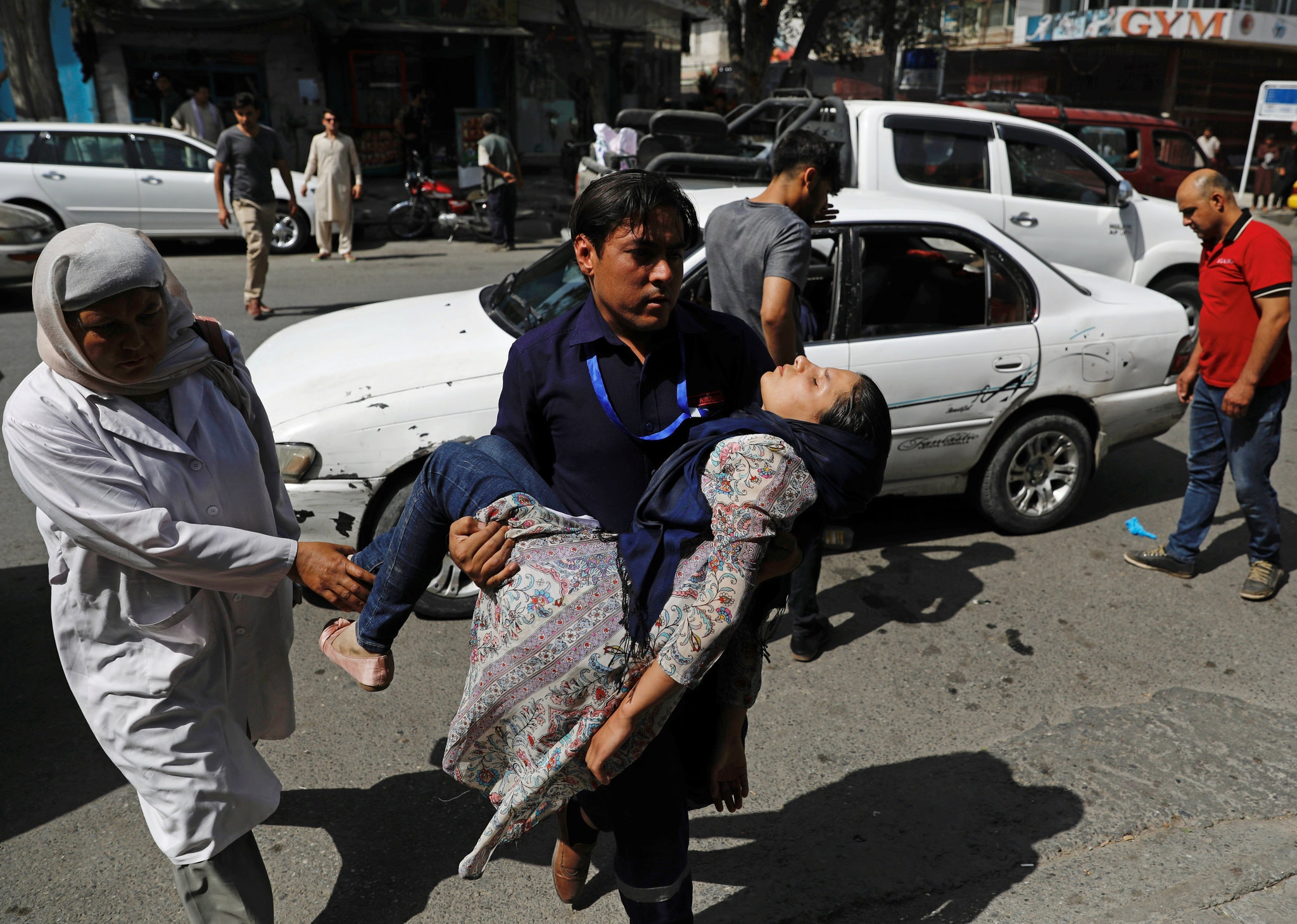 A man carrying an injured woman to a hospital after a blast in Kabul, Afghanistan, on Wednesday. Credit Mohammad Ismail/Reuters