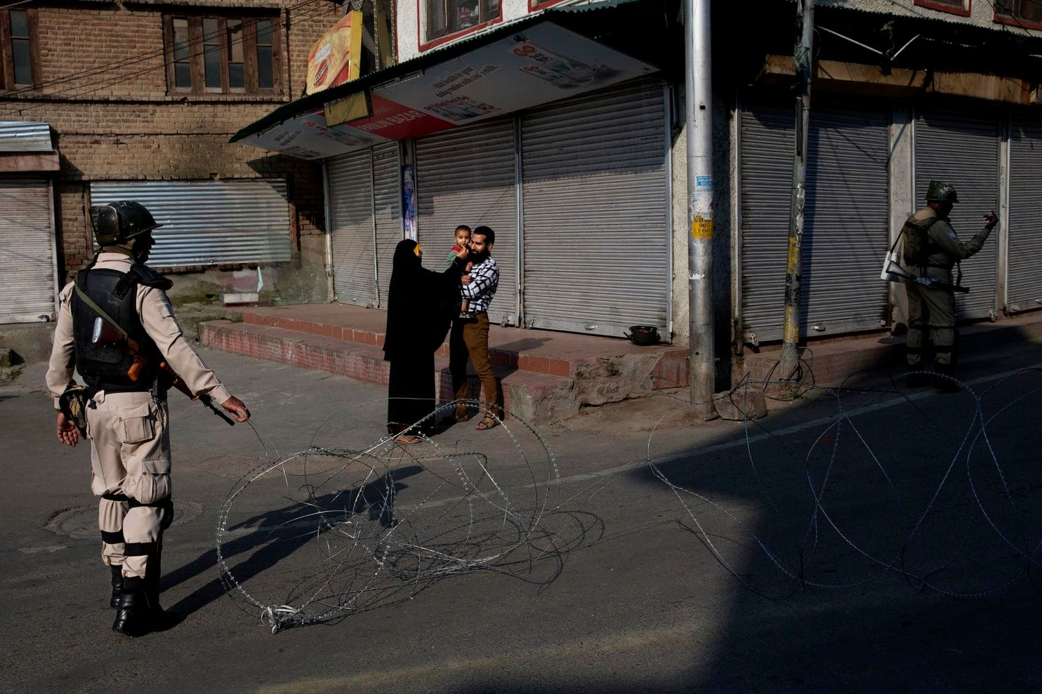 In this Friday, Aug. 23, 2019, file photo, a Kashmiri family waits for a lift to take their sick child to hospital as Indian paramilitary soldiers stand guard near a checkpoint during lockdown in Srinagar, Indian controlled Kashmir. India's top court is taking up legal challenges to the government's decision to revoke Indian-controlled Kashmir's special status and has asked the government to explain its stance to the court. The Supreme Court held a preliminary hearing on the petitions Wednesday, Aug. 28, and said five judges will start a regular hearing in October. (Dar Yasin, File/Associated Press)