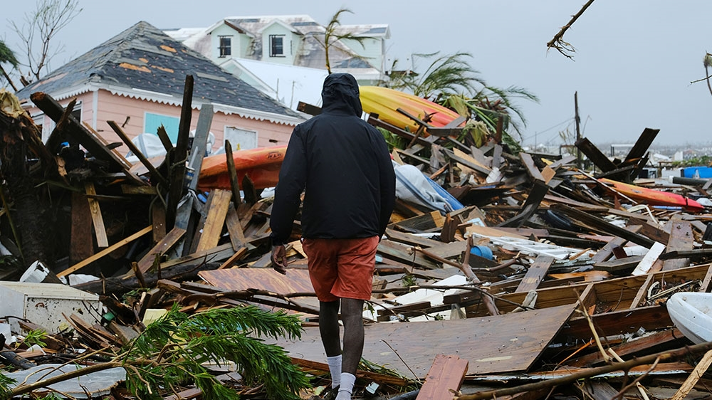 A man walks through the rubble in the aftermath of Hurricane Dorian on the Great Abaco island town of Marsh Harbour, Bahamas (Dante Carrer/Reuters)
