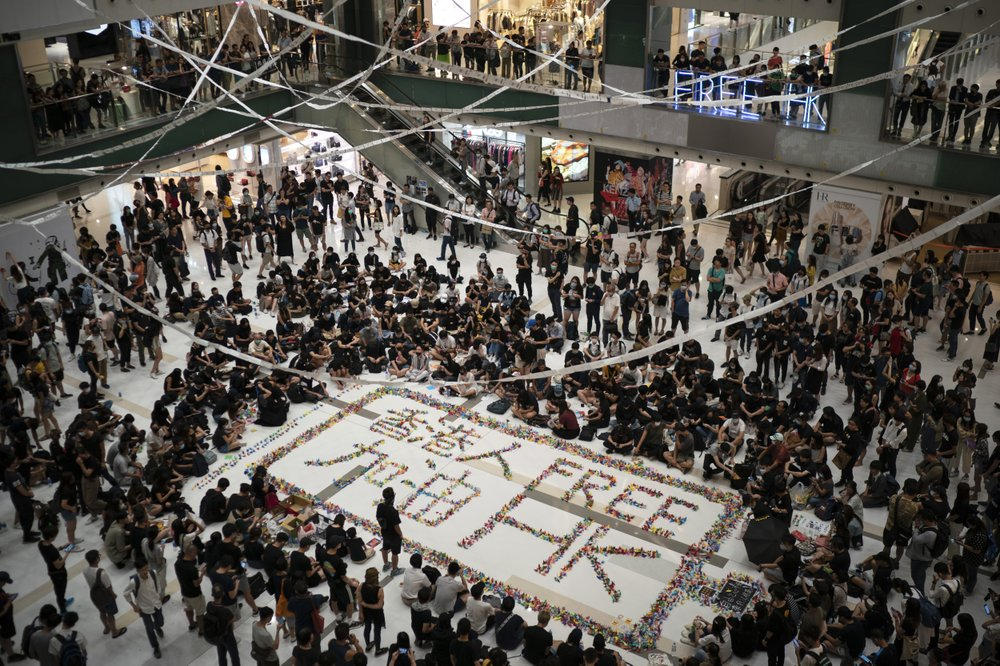 Residents gather at a shopping mall in Sha Tin to protest a teenage demonstrator shot at close range in the chest by a police officer and condemn police tactics and demand accountability, in Hong Kong, Wednesday, Oct. 2, 2019. The shooting Tuesday during widespread anti-government demonstrations on China's National Day was a fearsome escalation in Hong Kong's protest violence. The 18-year-old is the first known victim of police gunfire since the protests began in June. He was hospitalized and his condition was described by the government as stable on Wednesday. (AP Photo/Felipe Dana)