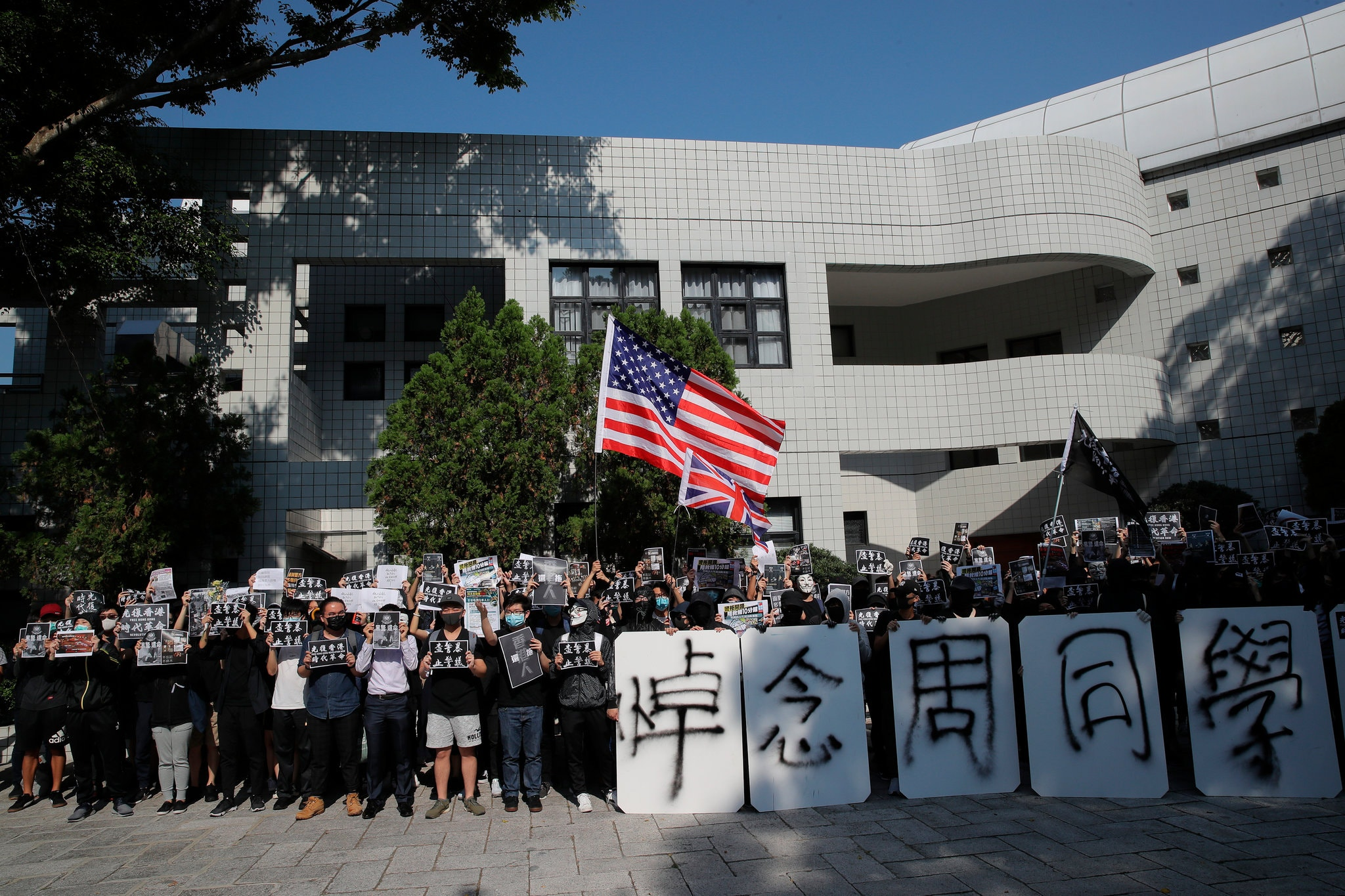 "Protesters with placards that read ""missing classmate Chow"" gathered Friday outside the home of the president of the Hong Kong University of Science and Technology. Credit Kin Cheung/Associated Press"