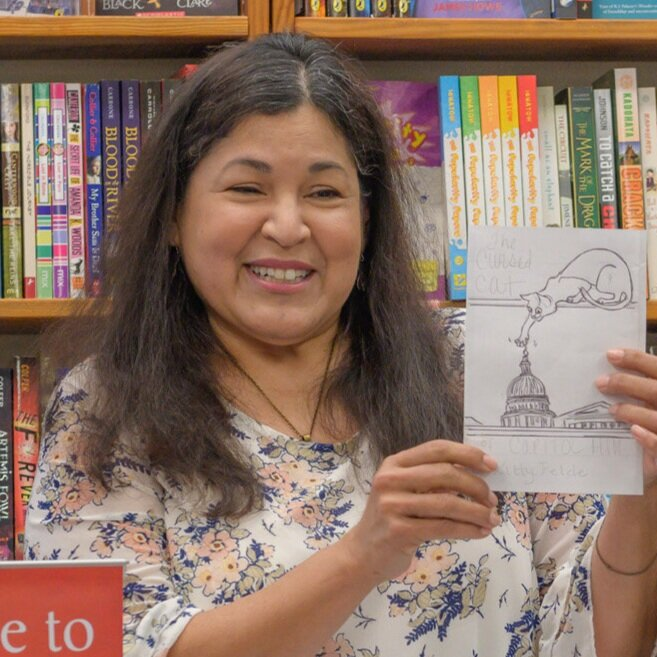 """Imelda Hinojosa - Tia Catalina    Imelda Hinojosa  is an artist and illustrator born and raised in Southern California. She illustrated the cover for """"Welcome to Washington, Fina Mendoza"""" and the logo for """"The Fina Mendoza Mysteries."""" She is a member of the Society of Children's Book Writers and Illustrator."""
