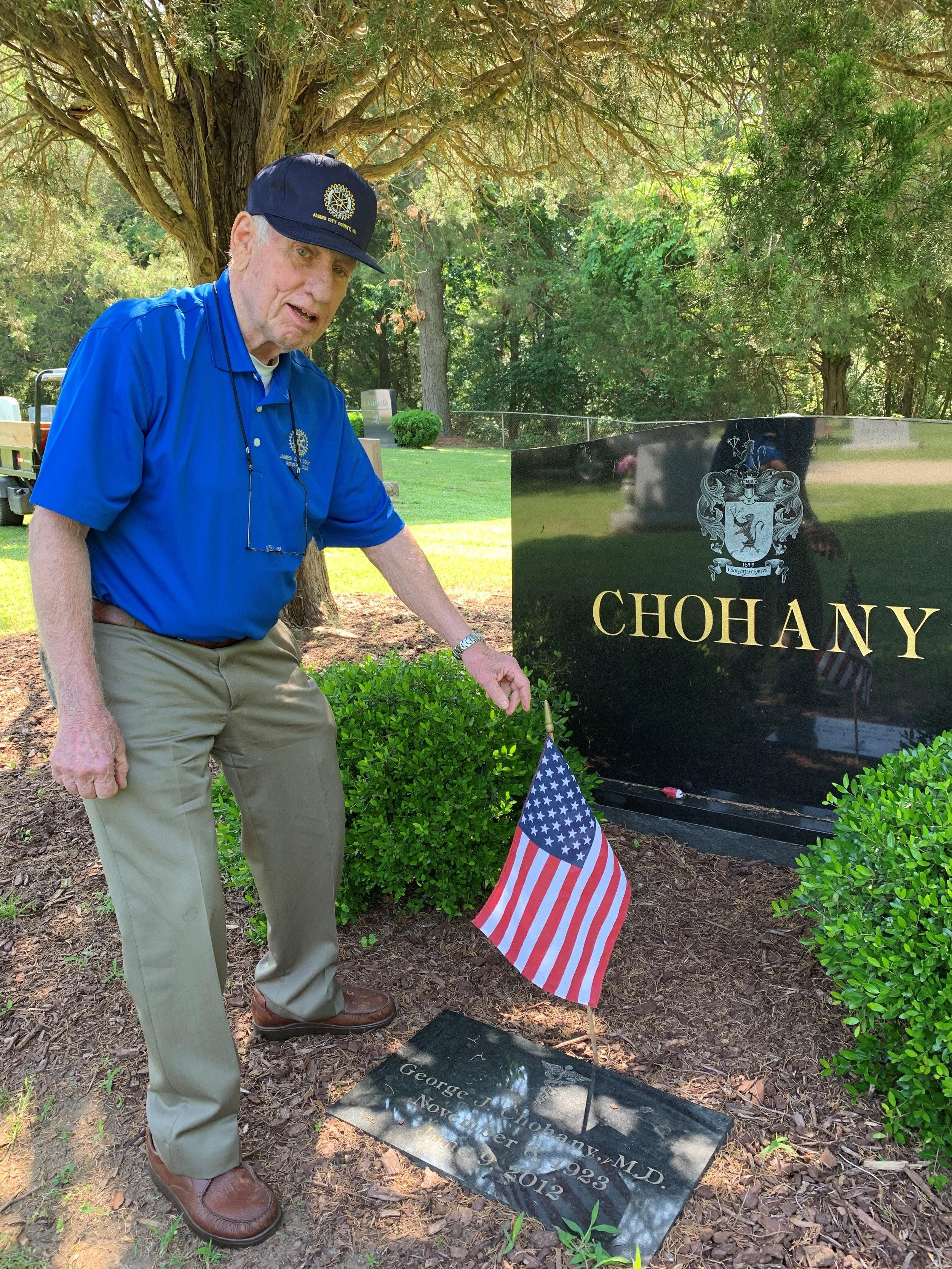 memorial day preps - Club member and veteran himself, John Bradish places a flag on a veterans grave for Memorial Day