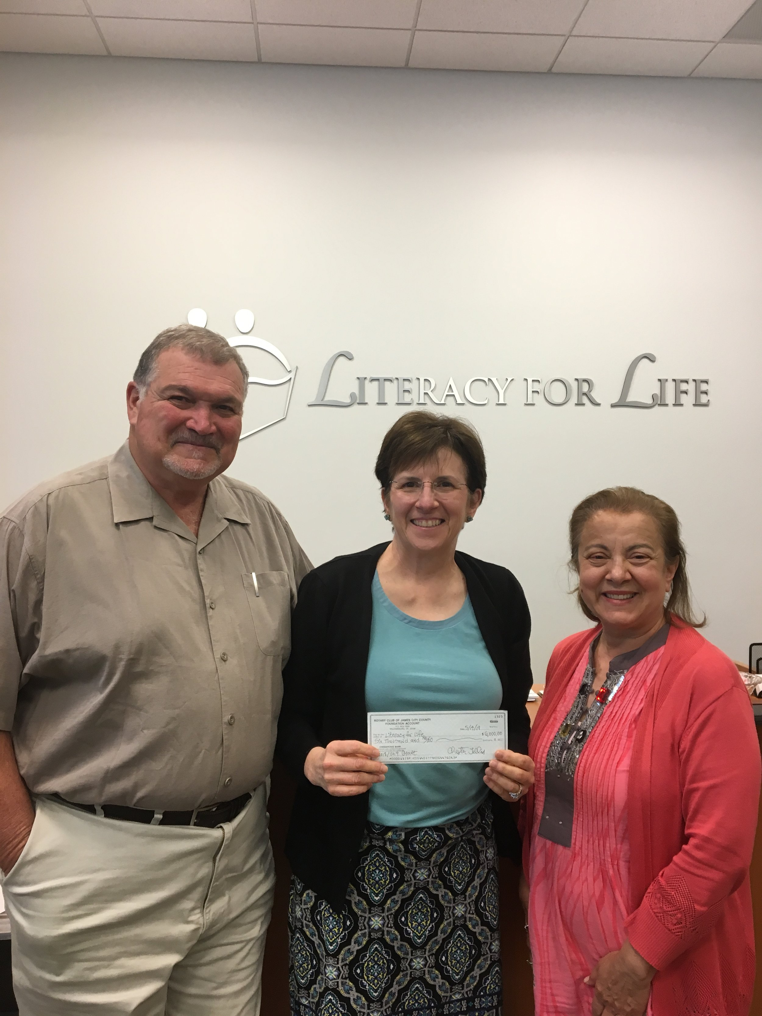Our club support - Club members Sal and Carmelina Trifeletti present a donation check to Joan Peterson (center), Executive Director of Literacy for Life.