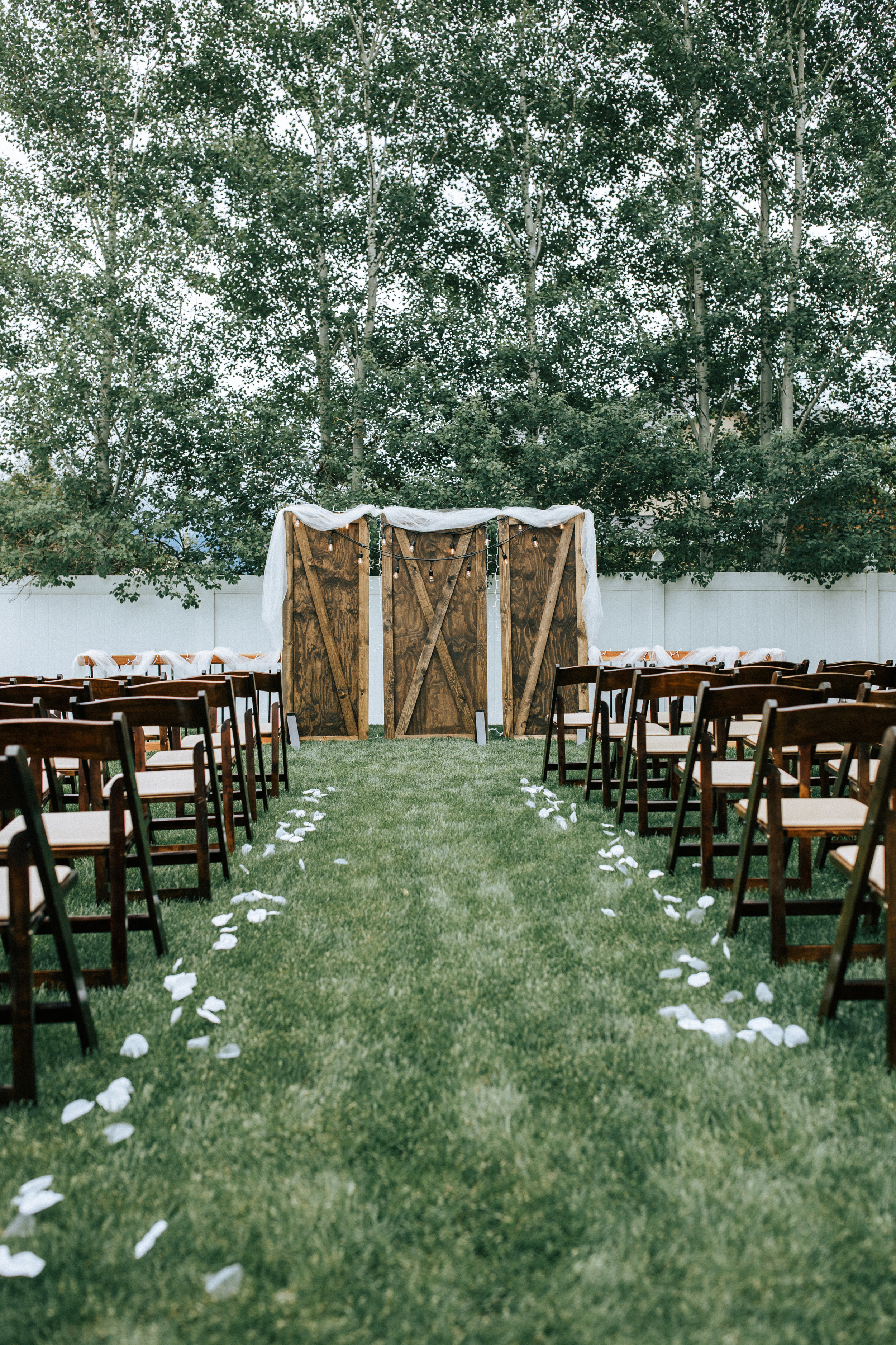Utah backyard wedding wood backdrop hanging lights