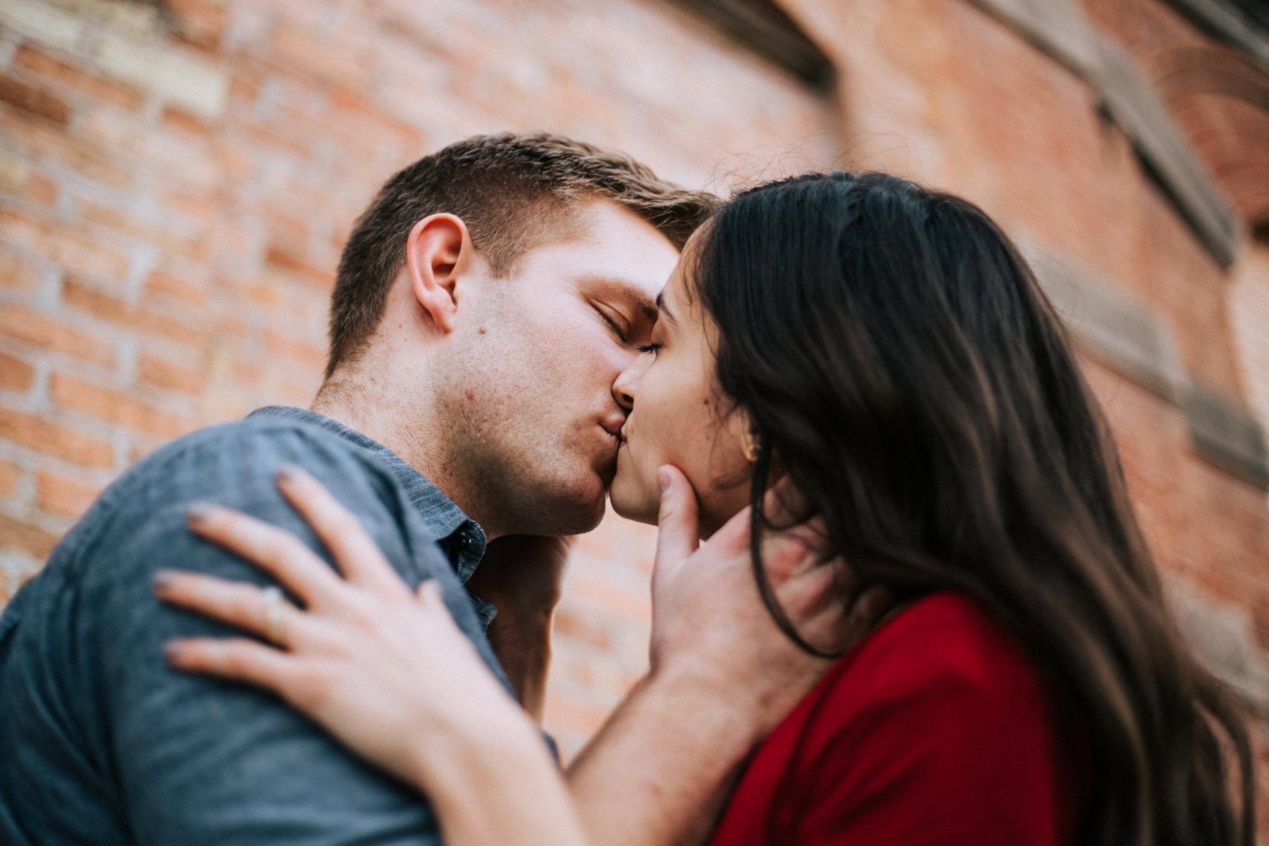 Downtown city couple portraits Utah romantic kiss