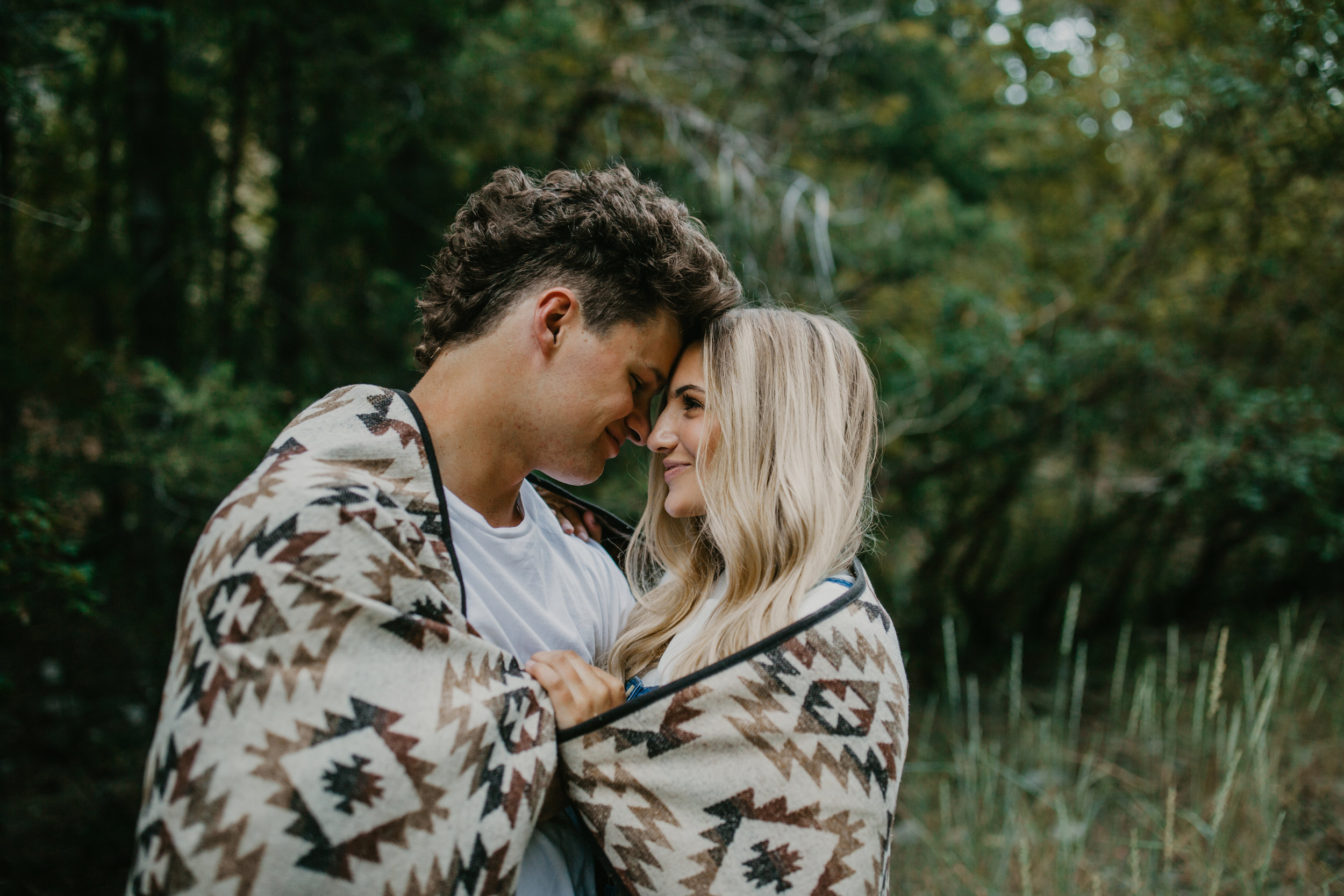 Romantic forest engagement session couple wrapped in blanket in Utah mountains long blonde hair