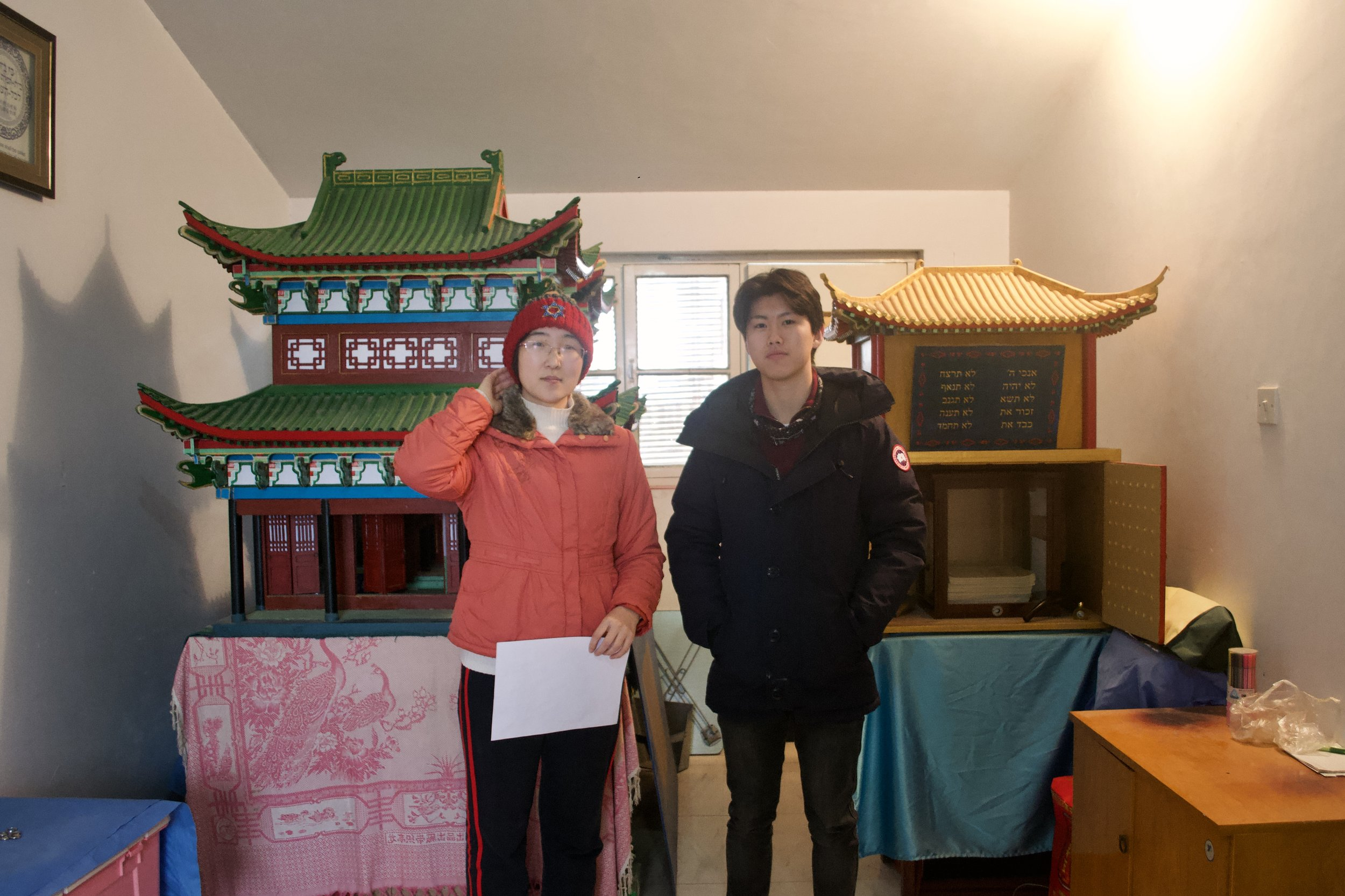 - Our founder, Nicholas Zhang, with a descendant of the Zhao family. Behind them stand the miniature replica of the destroyed Kaifeng synagogue (left) and Torah Ark (right). [Nicholas Zhang Archives]