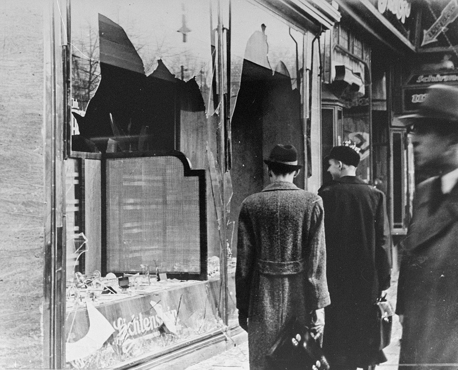 Germans walk by a Jewish business destroyed on Kristallnacht.  [Public Domain]