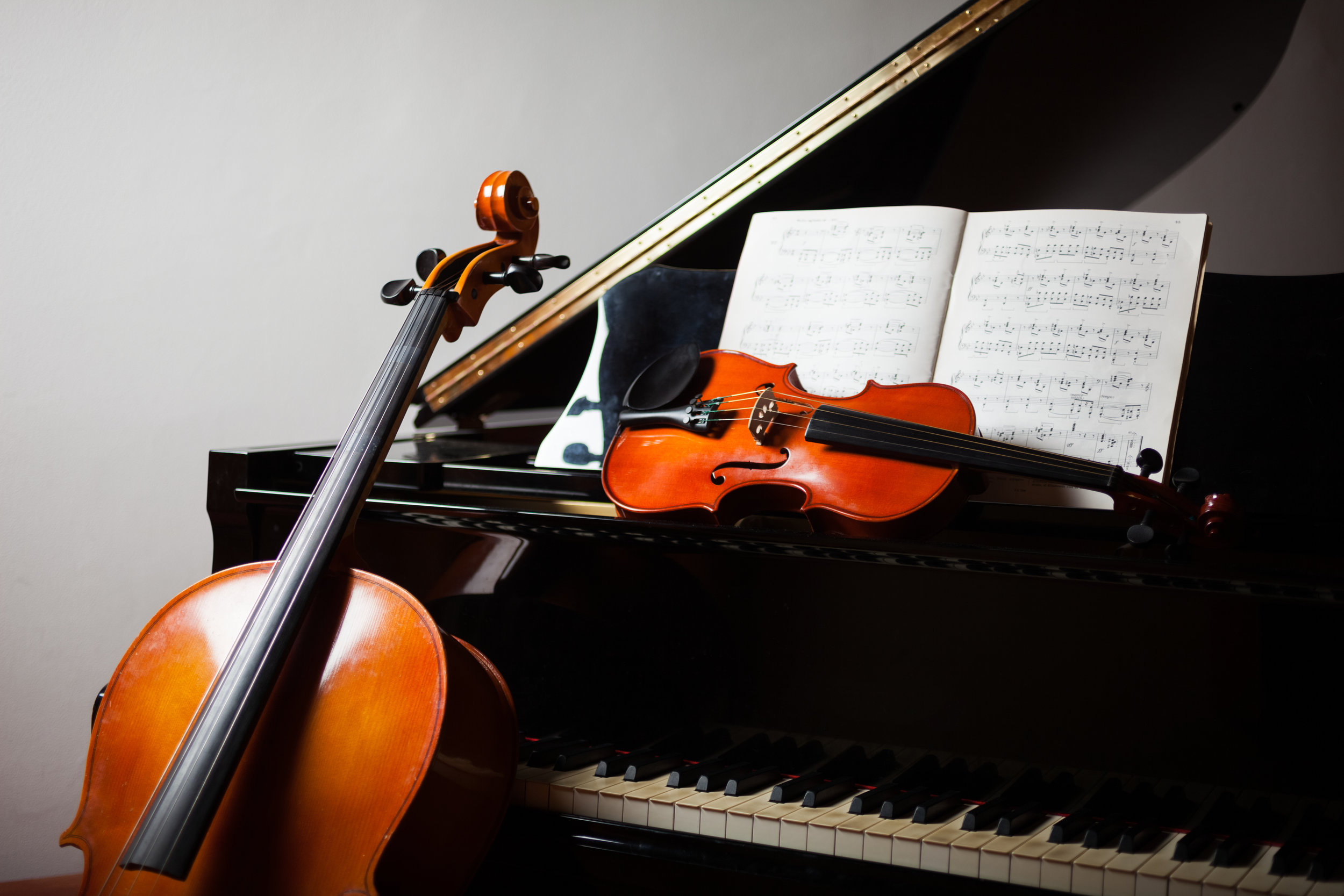 Piano with a cello resting against it and a violin and open piece of music on top of it