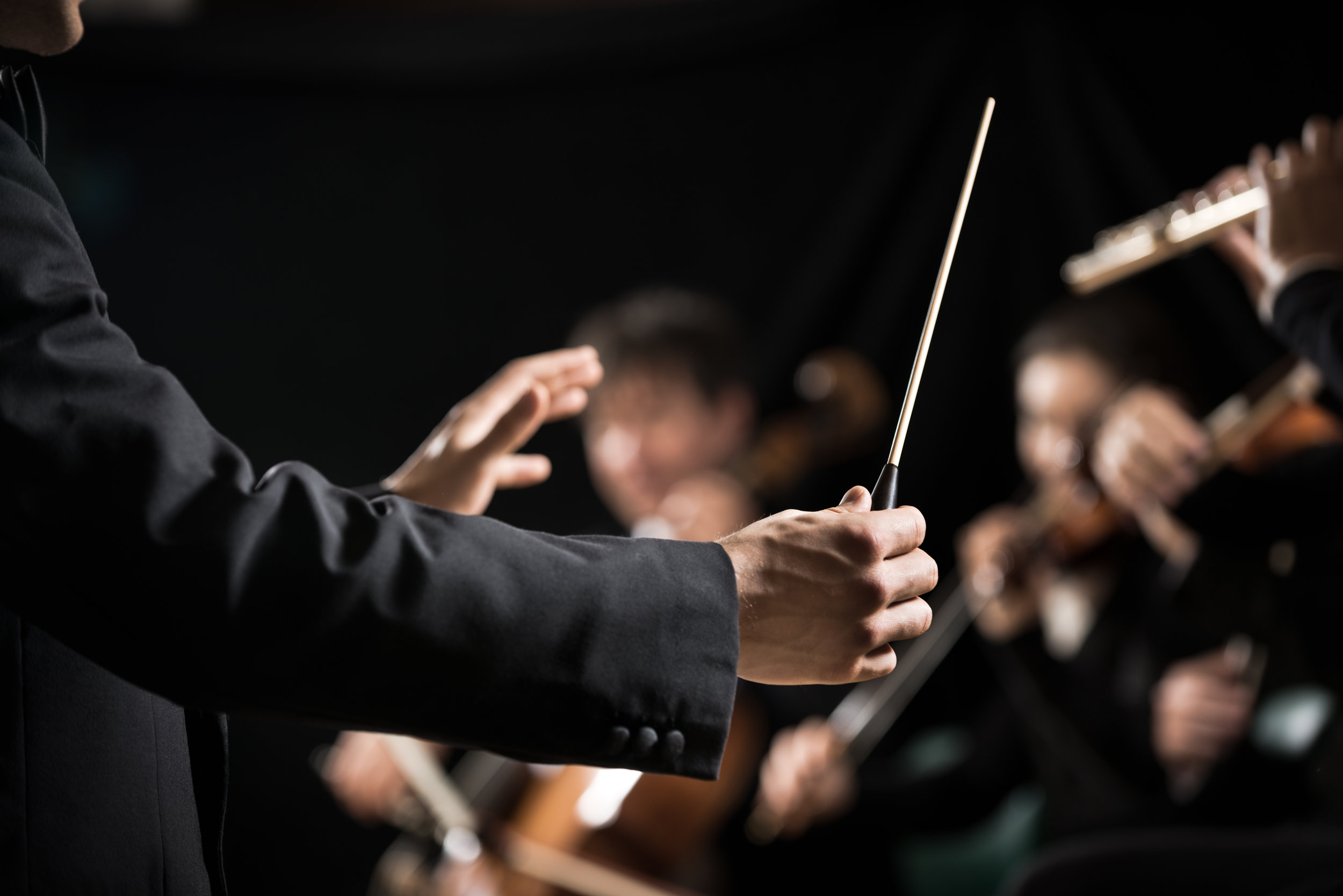 Conductor standing in front of an orchestra with baton in hand