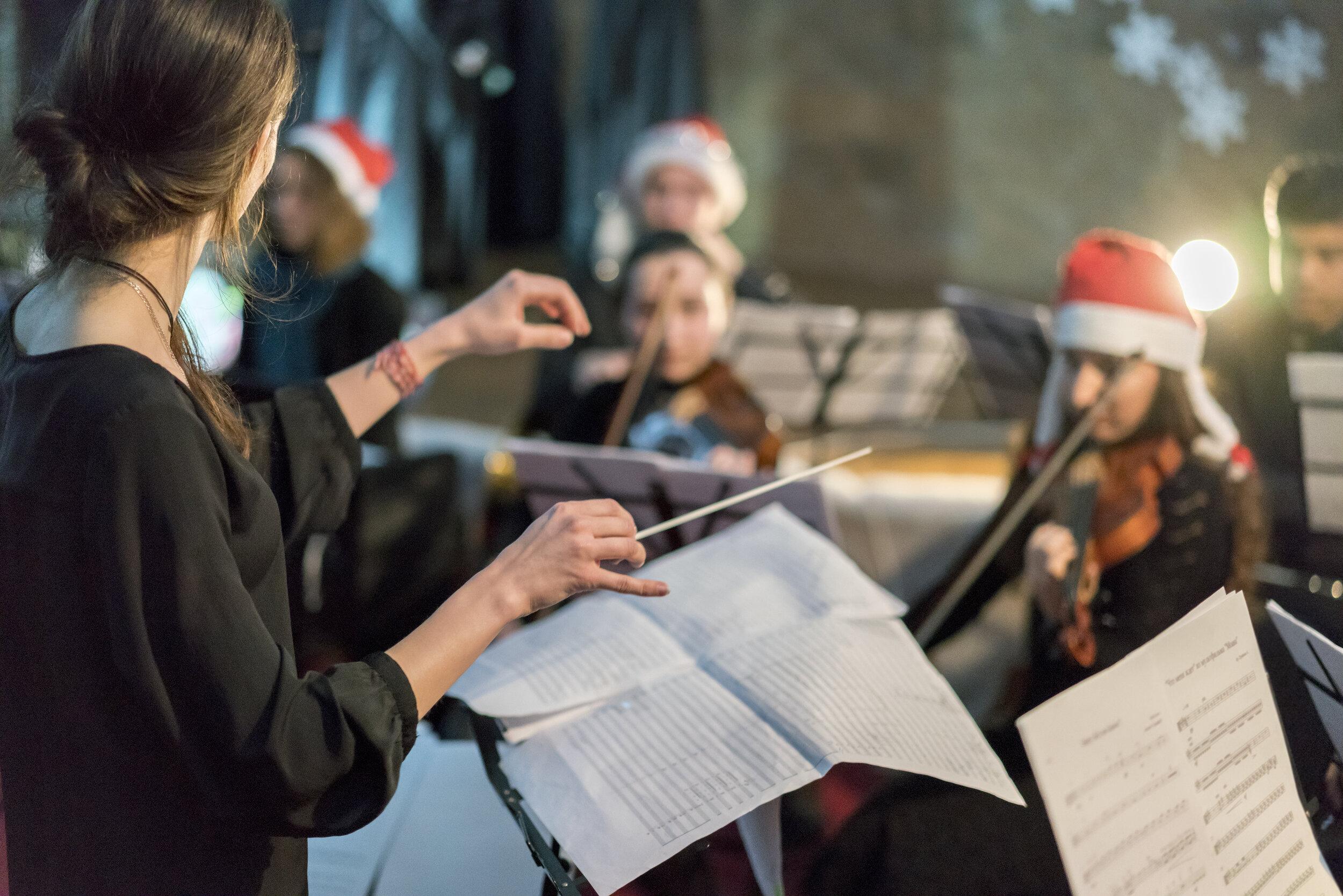 Classical string orchestra wearing Santa hats