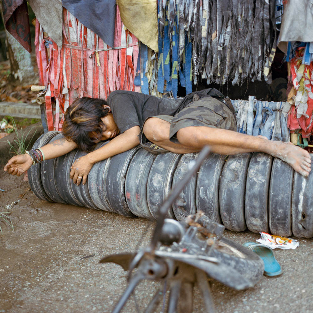 A scooterist sleep on vespa's tires after a long haul journey anticipating a vespa event in Banda Lampung, Sumatra.