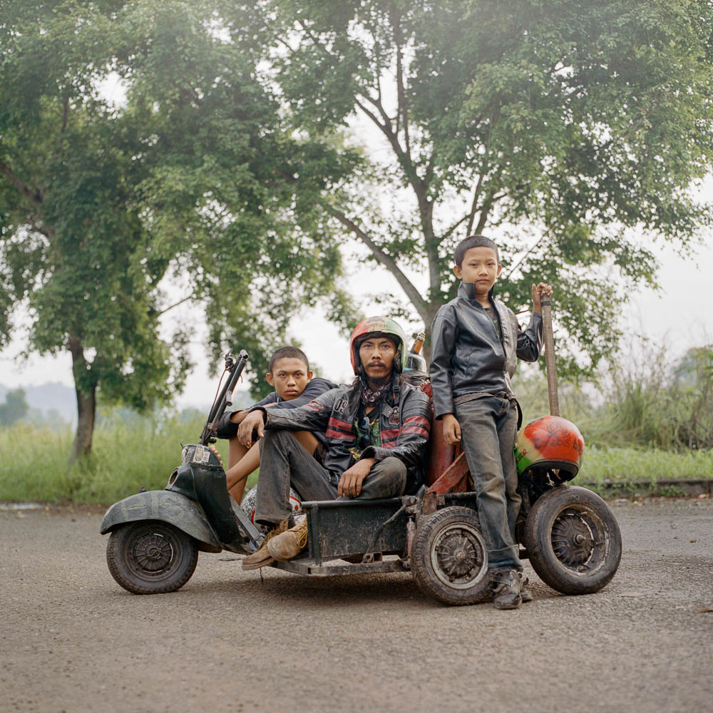 Iponk (middle), a scooterist from South Sumatra along with his son (right) and a travel companion (left). He traveled for hundreds of kilometers, mostly at night to avoid police, to attend a Vespa event in Lampung.