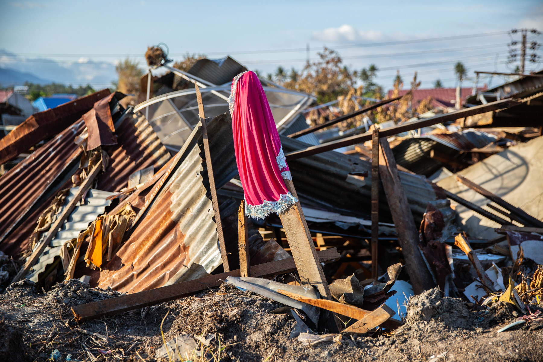"""A sign put on the ruins at Balaroa, Palu, Central Sulawesi. On Friday afternoon Sep. 28, 2018 Central Sulawesi hit by deadly earthquake that triggered tsunami and liquefaction that destroyed many places. Amid the ruins of Balaroa housing complex I met Huzaimah (38), one of the survivors of the disaster. Her eyes filled with tears as she told me how she could escape death. When the earthquake struck, a cupboard fell on her but luckily she was able to remove it, and then she immediately got out of the house. Sadly, her elder sister was lost amid the stumbling ground and had not been discovered when I met her. """"That's why we put a sign there (pointing to the flag placed on the ruins) in the hope to find my sister even though she might have been dead"""", she said. When I was walking around the area, I found some similar signs, signifying a hope that the search and rescue team would be able to find their relatives or loved ones. According to the national disaster mitigation agency death toll had risen to 2,113 with 1,309 still missing and the official search was stopped on last Friday, Oct 12, 2018."""
