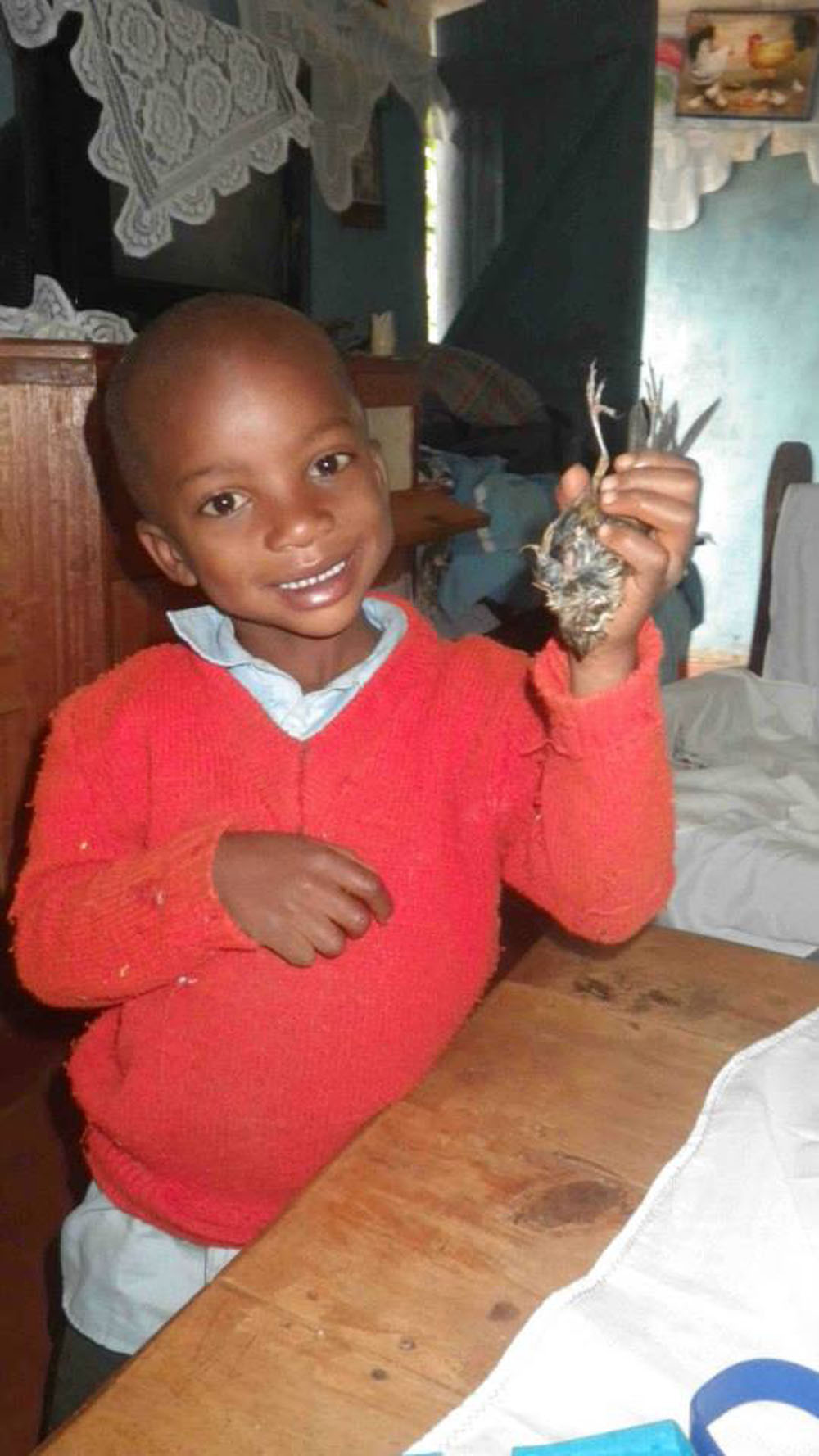 Arrive's youngest orphan, Onyoni, proudly shows off a bird he caught.