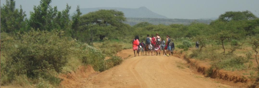 Maasai tibesmen and Arrive volunteers walking together through Maasailand.