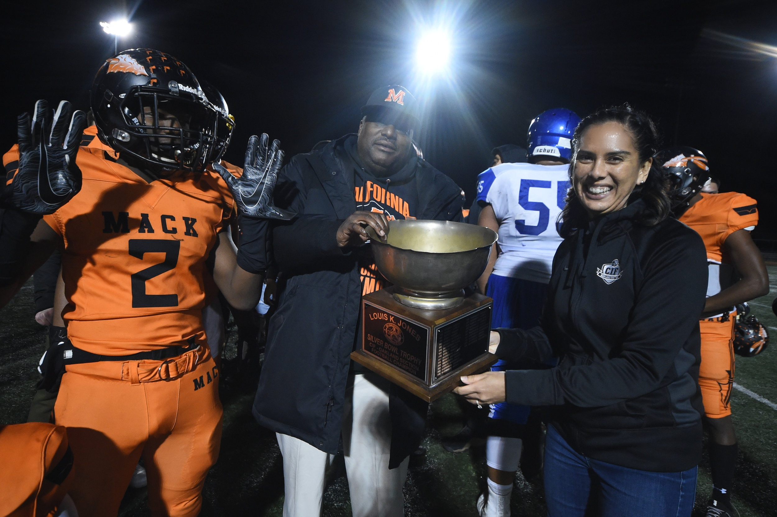 Phillips handing the Silver Bowl trophy to McClymonds High School head football coach after they won the championship.