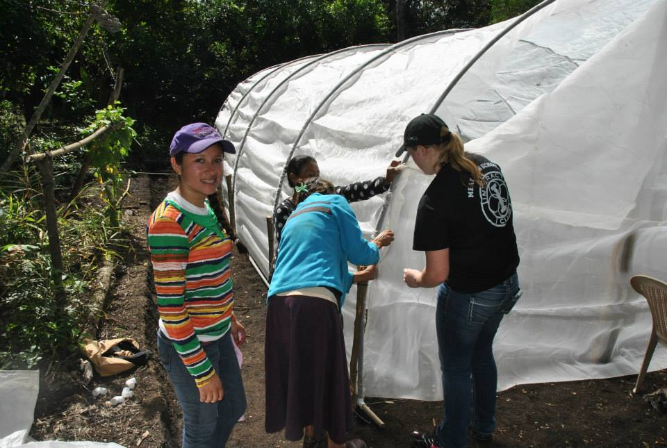 Namlo Field Coordinator Rosario Velasques, international volunteer help a local family build a greenhouse in Nicaragua.