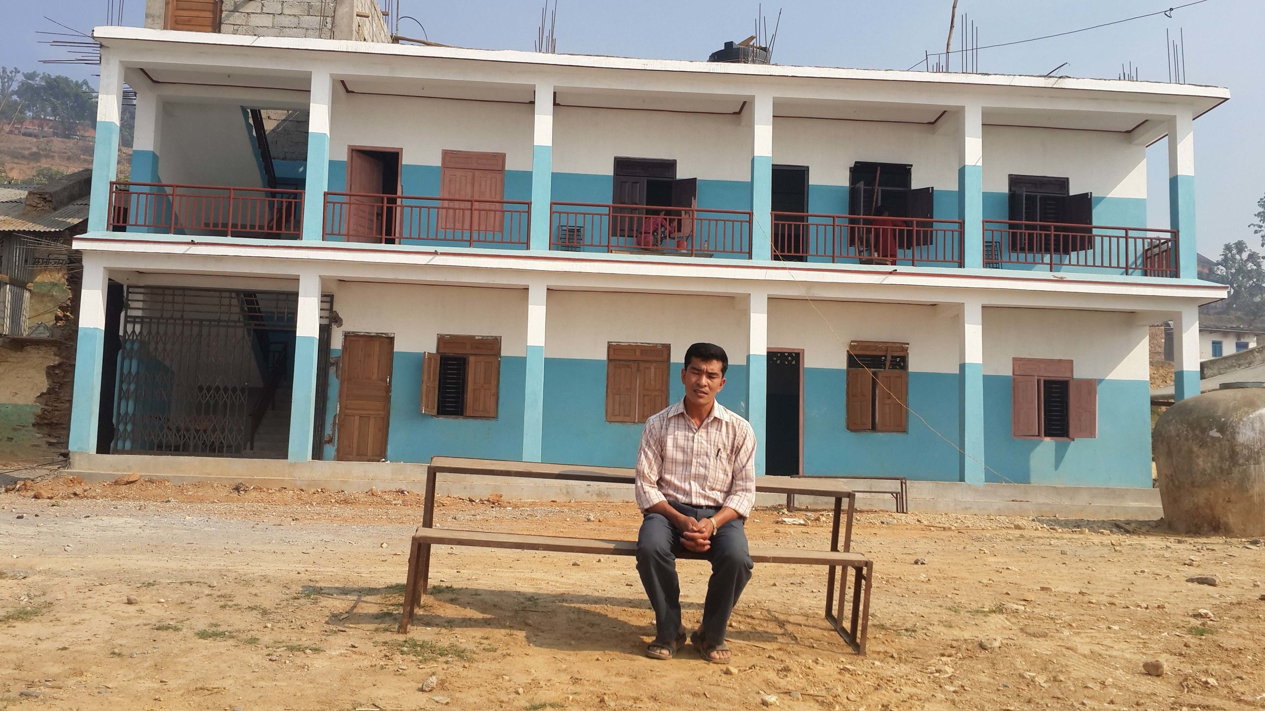 Community teacher in front of new Khamdenu school block.