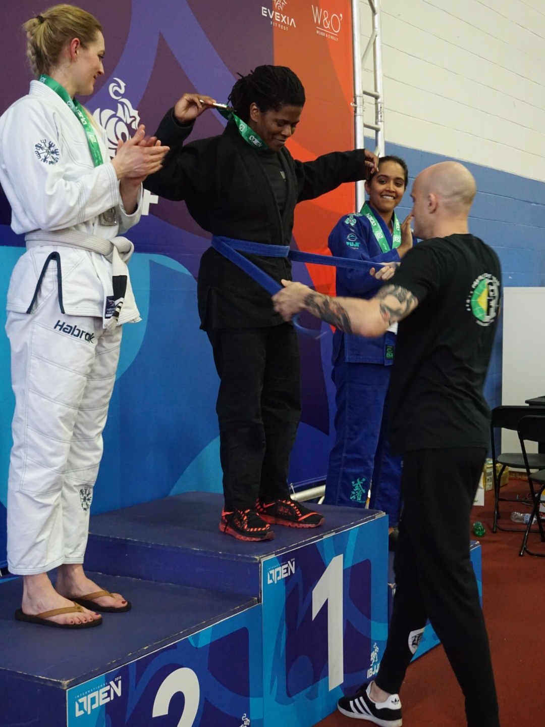 For her dauntless efforts and consistent training, Sydney Portis earned her blue belt on the podium following her matches.