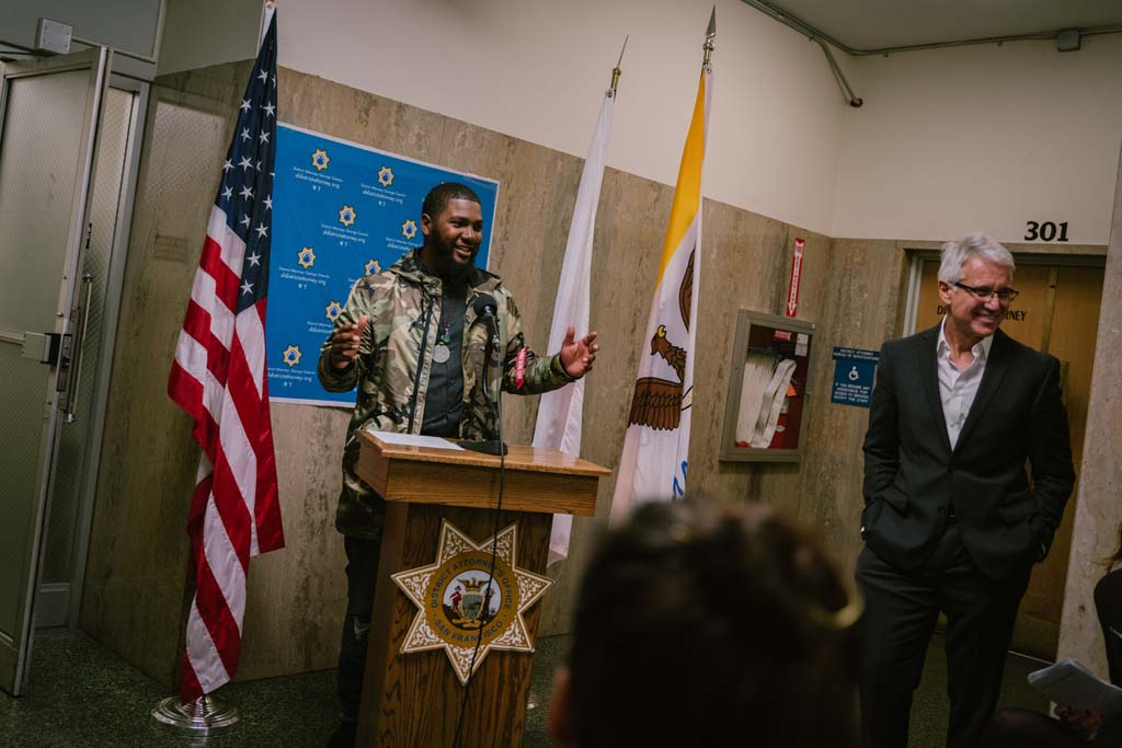 Workshop student Eugene Riley speaks during the opening reception of Visions of Justice alongside San Francisco District Attorney George Gascón at the Hall of Justice.