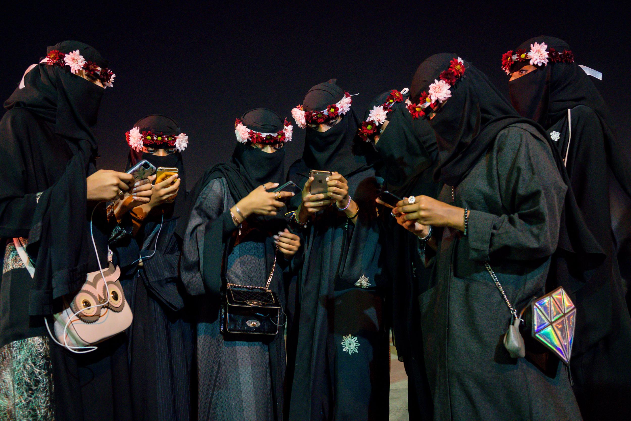 Saudi Arabia – Aug 1, 2018: A group of relatives busy on their social media phone applications, at Al-Jenadriyah, a cultural festival in Riyadh. Photo by: Tasneem Alsultan