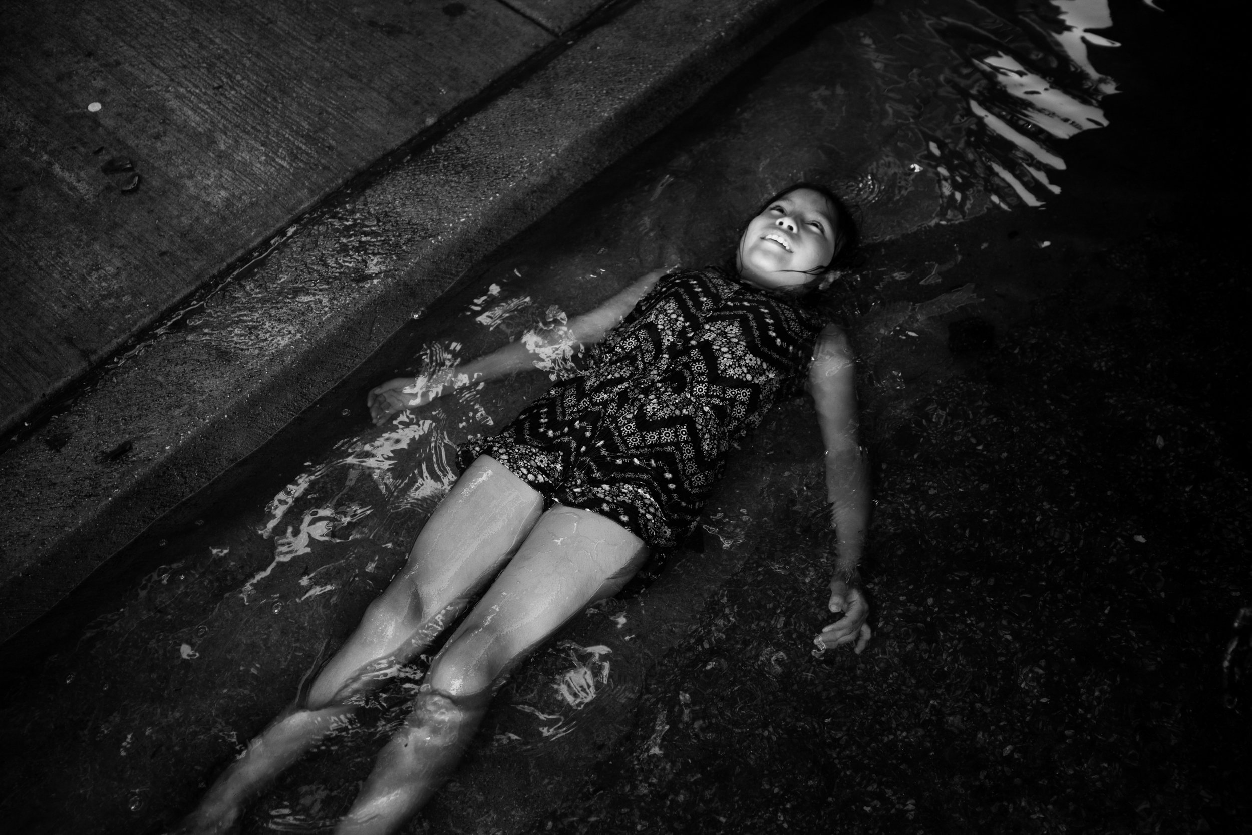 A child is taken by the current of a street filled with water during a hot summer day in Pilsen. A few fire hydrants in a block radius are usually opened by the neighborhoods gang members, after, children and families call gather to take advantage of the cool water. (Sebastián Hidalgo)