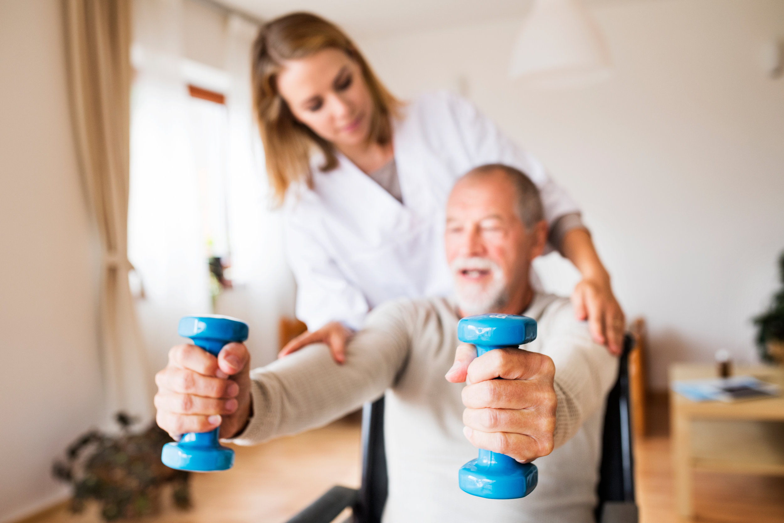 Woman working with a man in physical therapy.