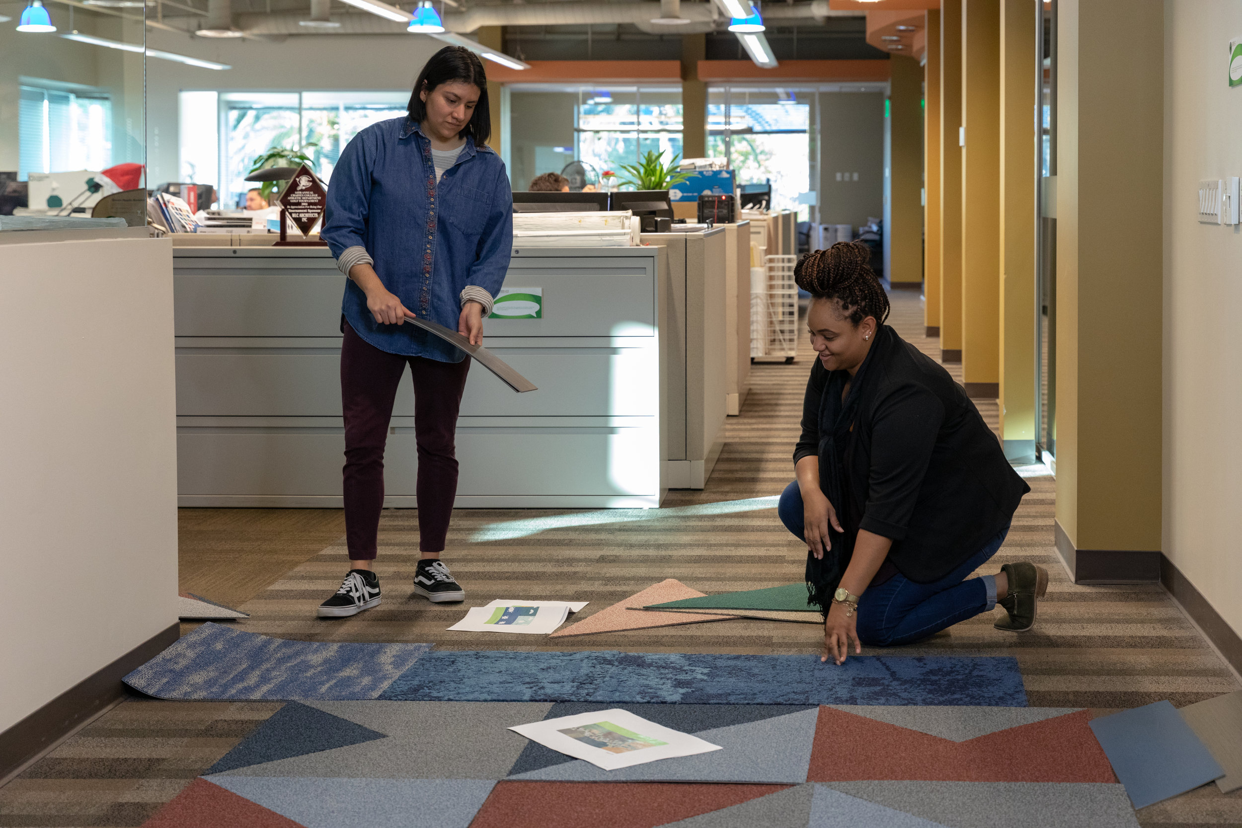 Designers Candace Luckett and Daniela Martinez lay out carpet samples during flooring design.
