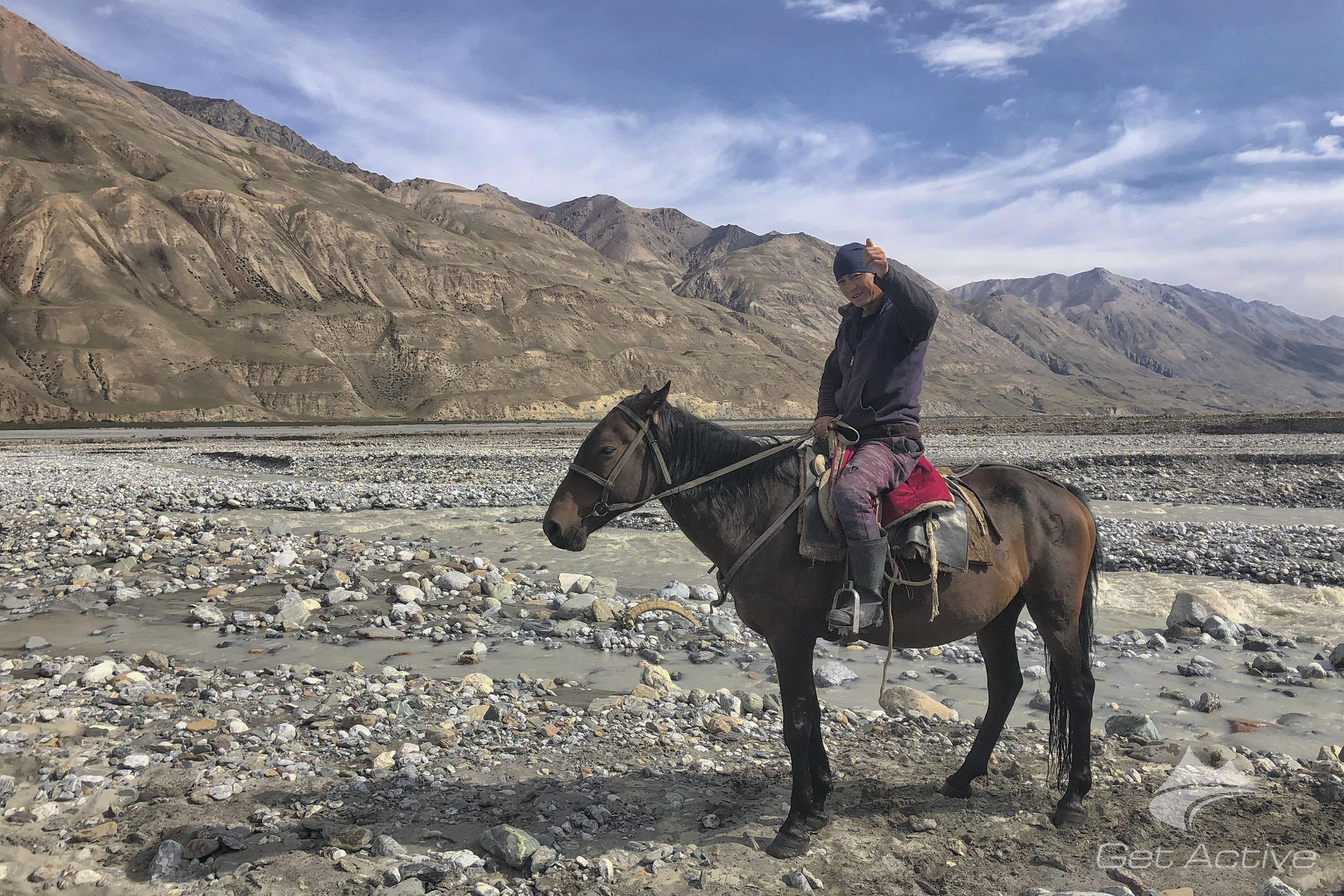Místní nomád přepravující turisty přes zrádnou řeku At-Jailoo