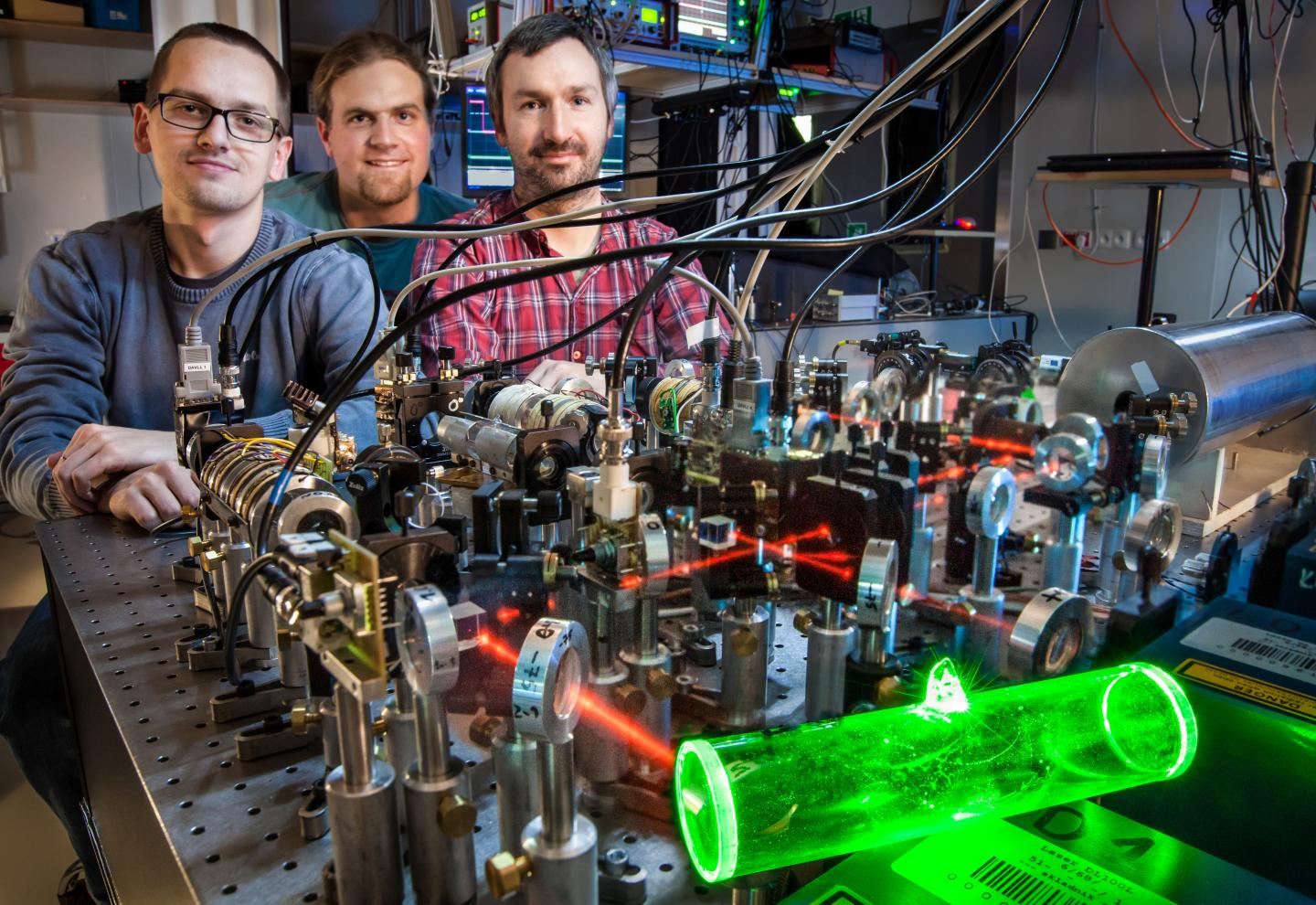 An atomic memory (glowing green), made at the Faculty of Physics at the University of Warsaw, can be used to store quantum information in telecomunication purposes.
