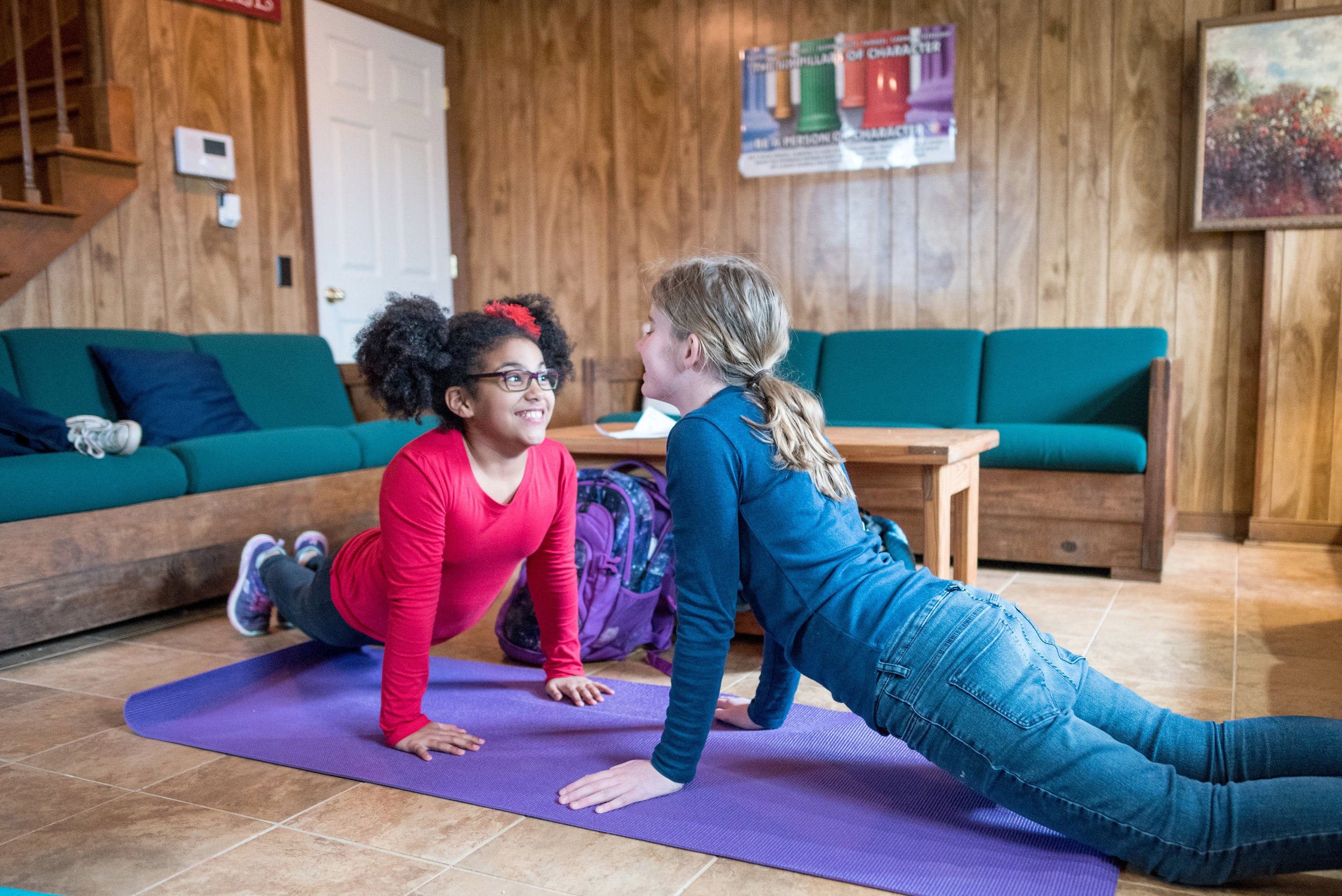 Two Oakland School students practice yoga in the dorms.