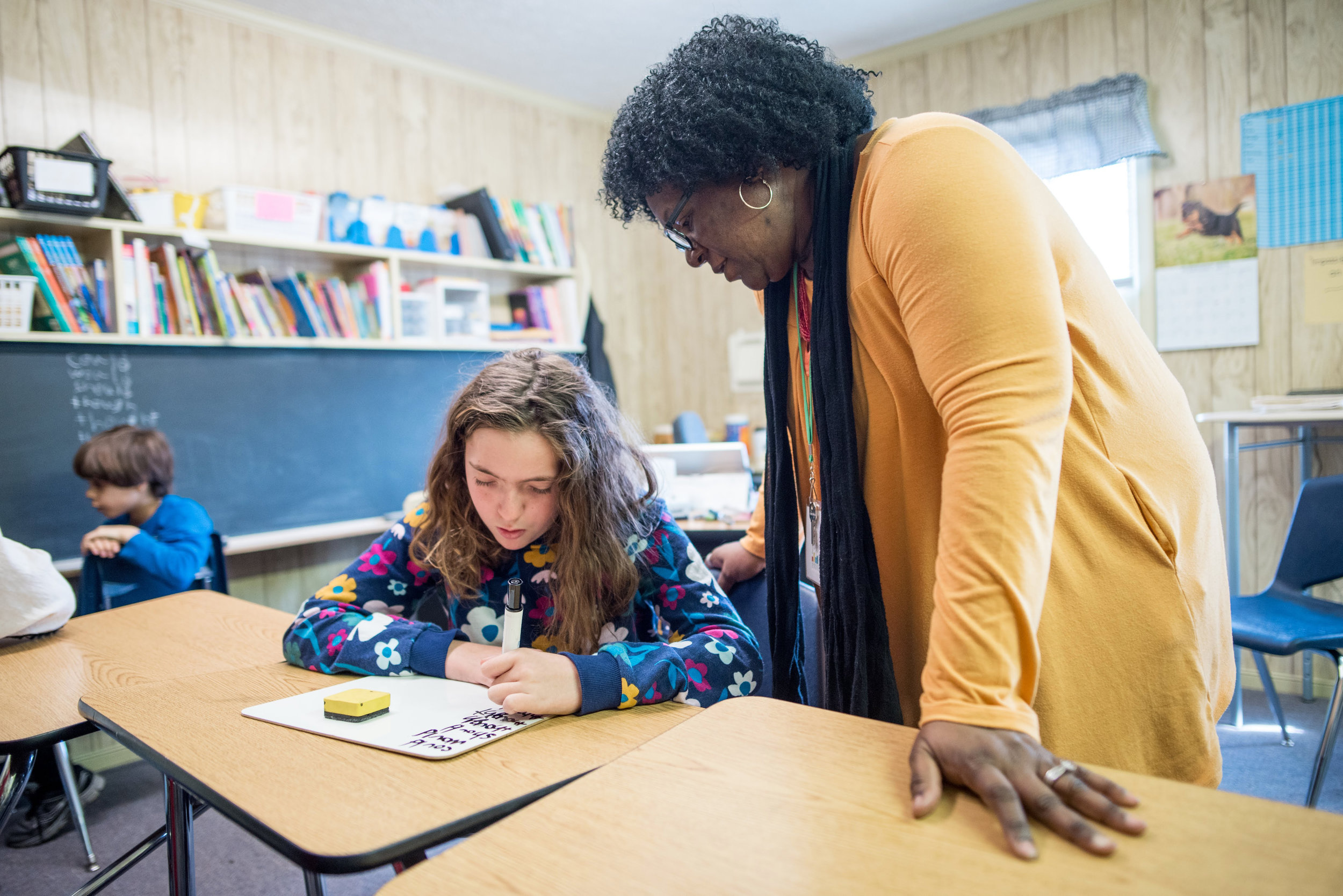 A teacher provides specialized 1:1 instruction to her student.