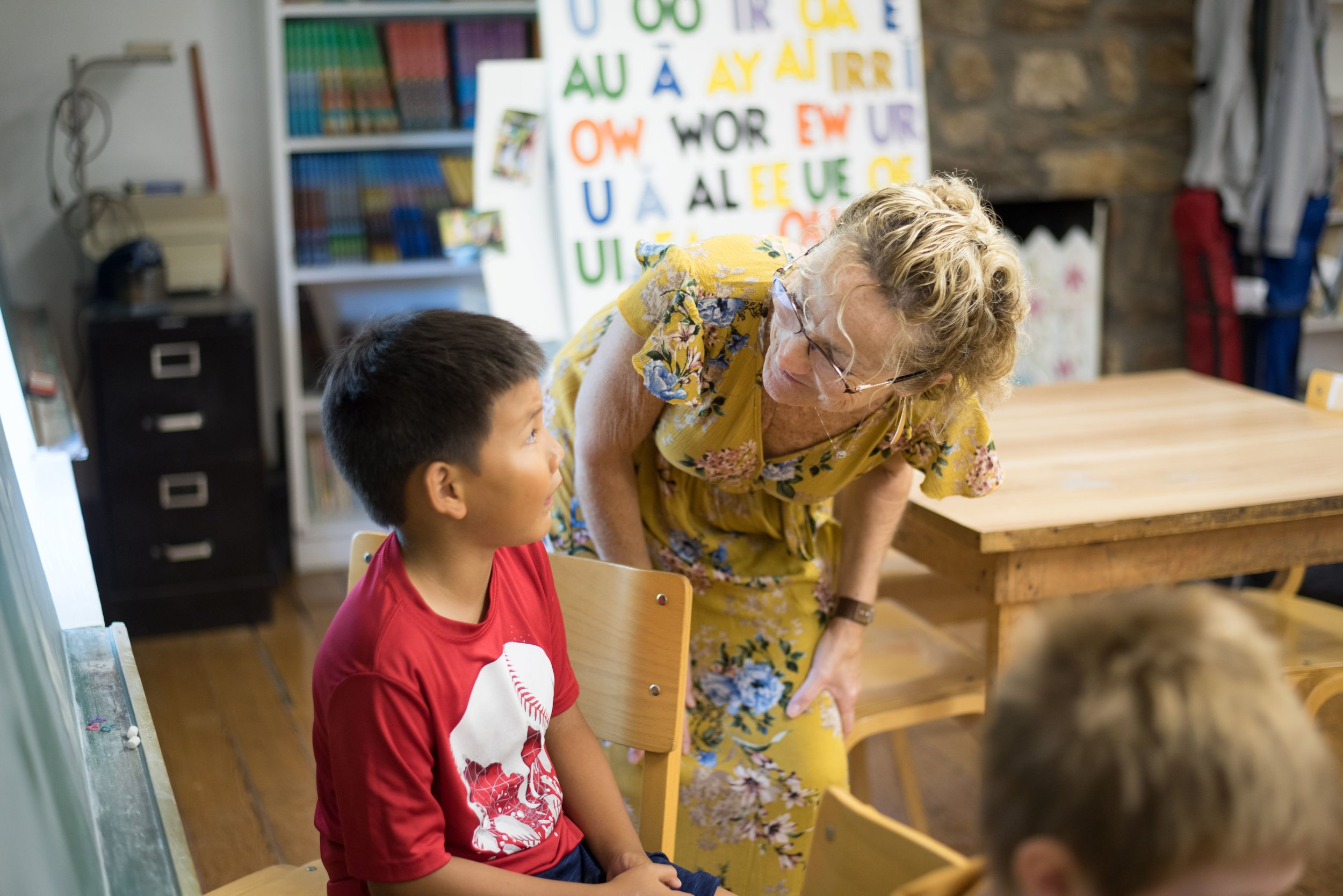 A teacher smiles at a student during Oakland's summer camp classes.