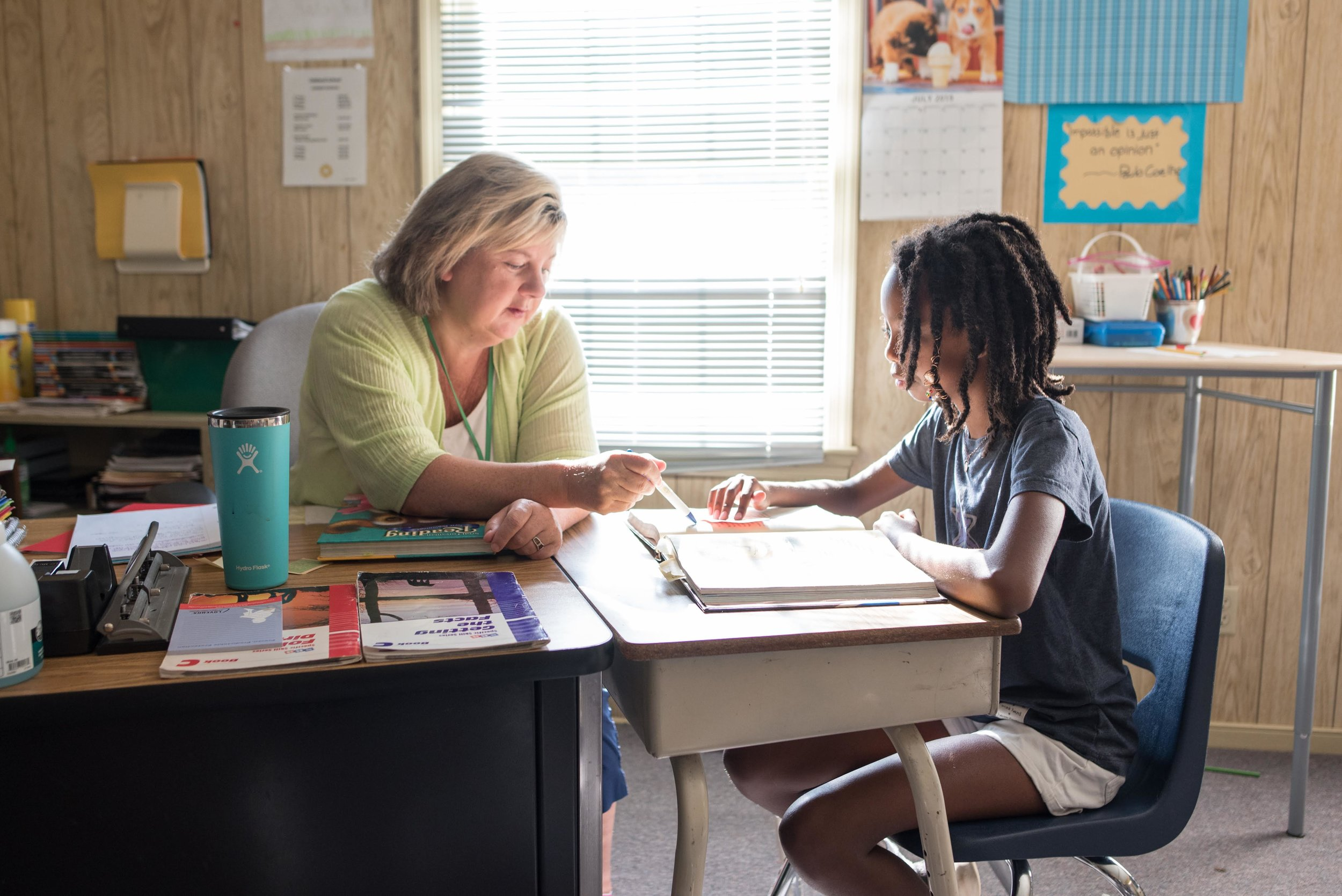 A teacher helps a student with specialized reading techniques during summer camp classes.