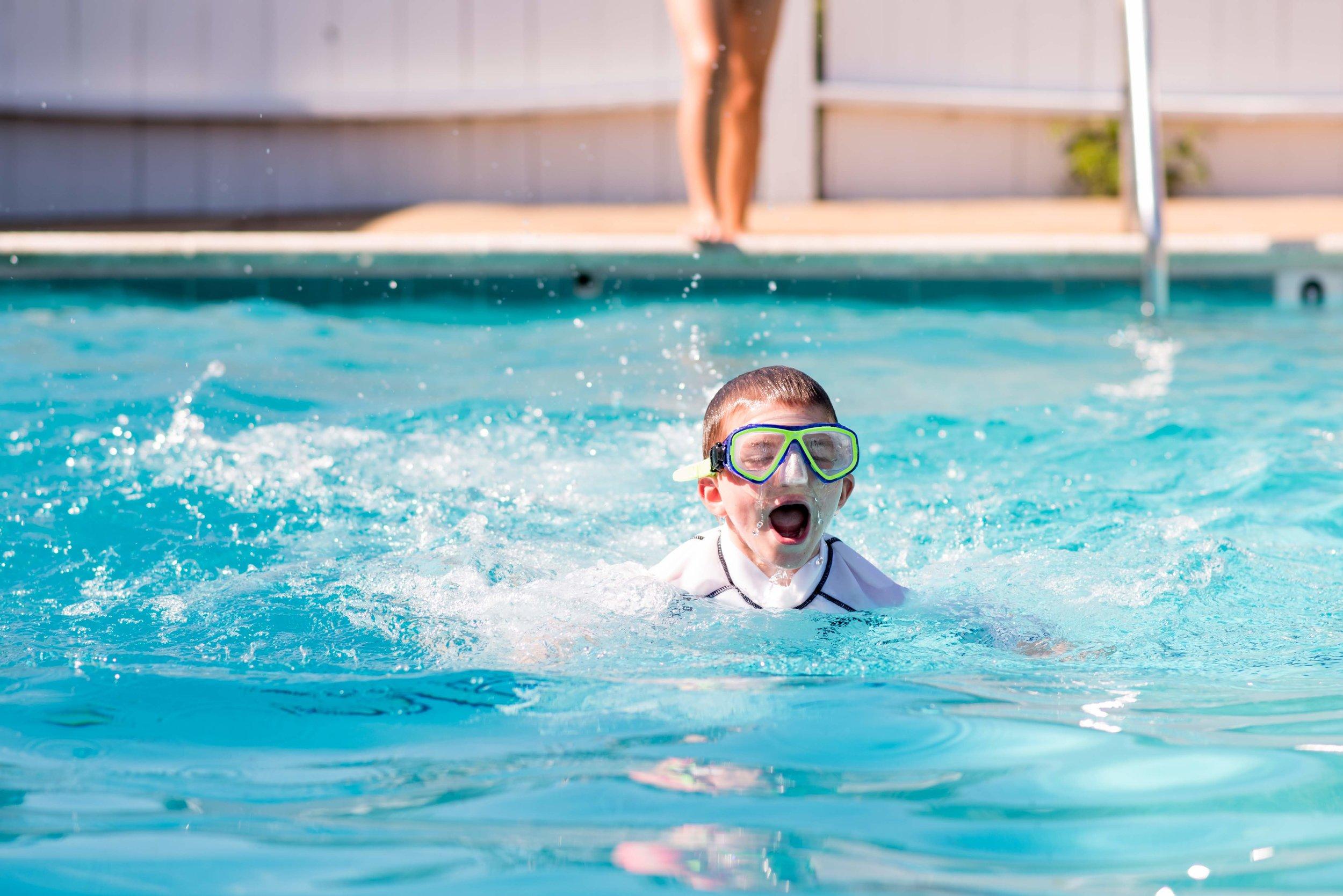 An Oakland camper swims across the pool in snorkeling gear.